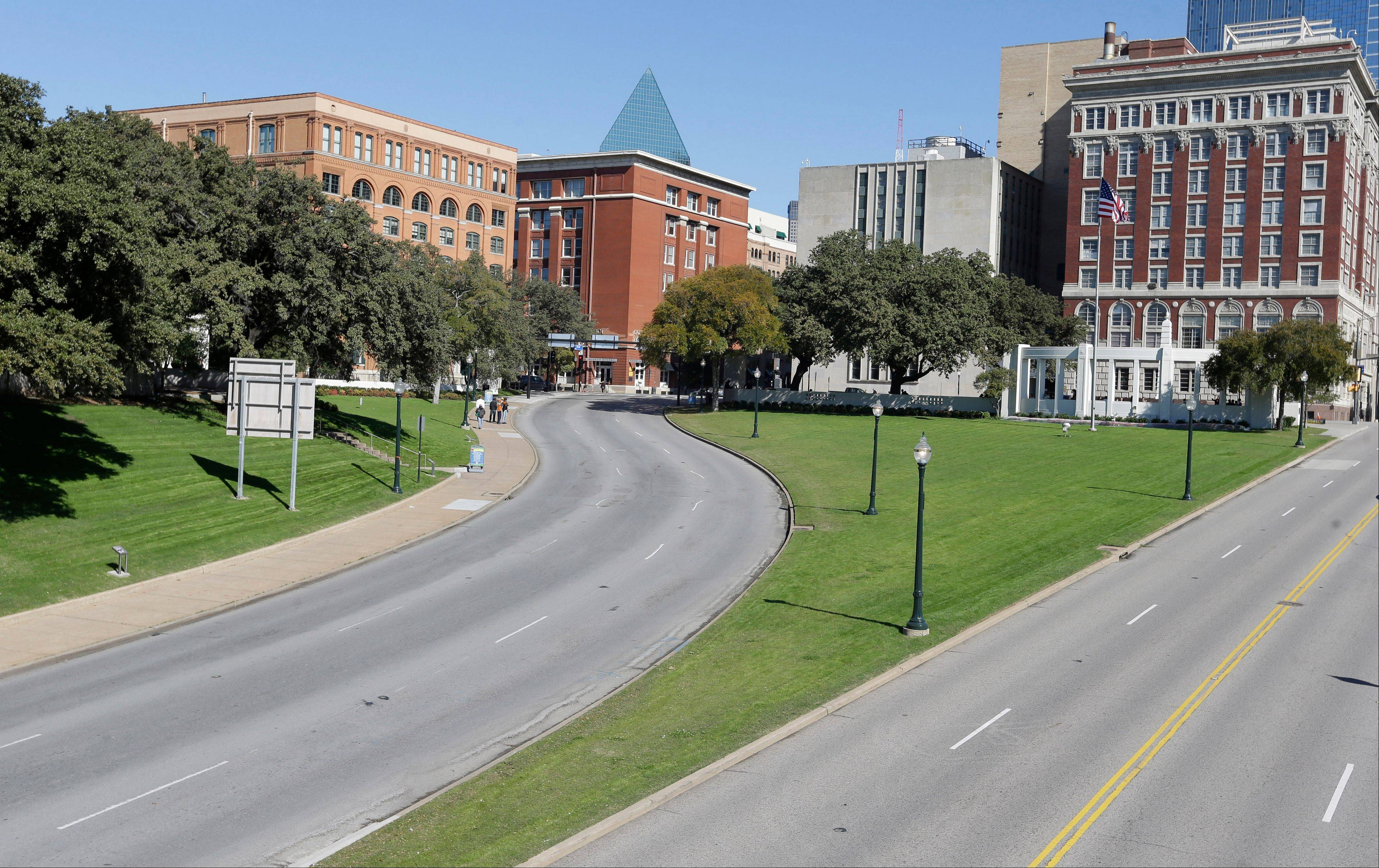 The former Texas School Book Depository building, left, now known as the Sixth Floor Museum, overlooks Dealey Plaza in Dallas. This is where Lee Harvey Oswald fired from, killing President John F. Kennedy on Nov. 22, 1963.