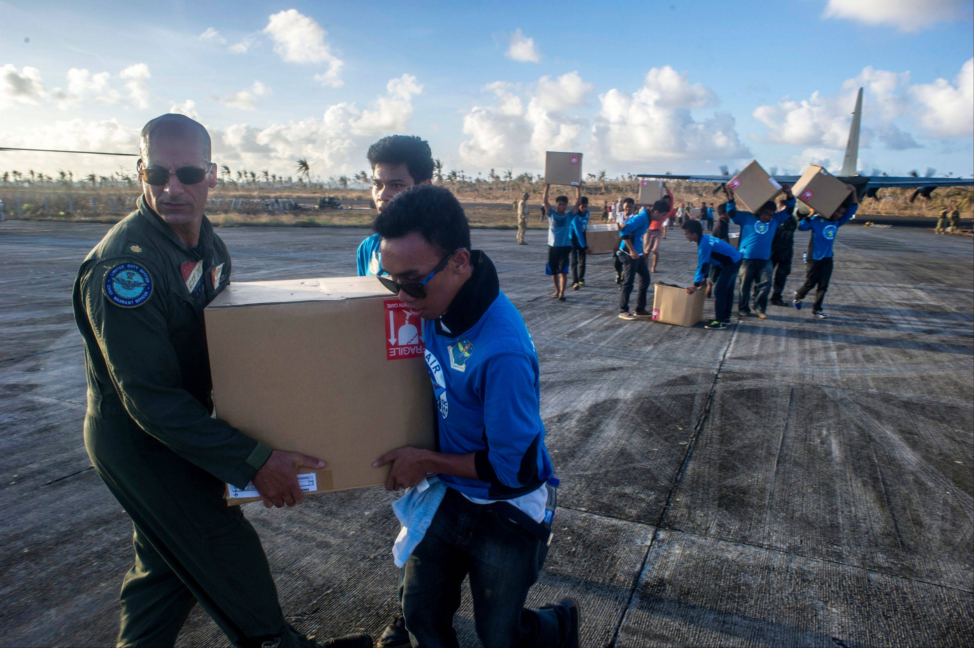 Lt. Cmdr. Mike DeVito, left, aboard the aircraft carrier USS George Washington, helps a member of the Filipino Air Force carry a box of relief supplies in support of relief efforts in the aftermath of the Super Typhoon Haiyan on Saturday.