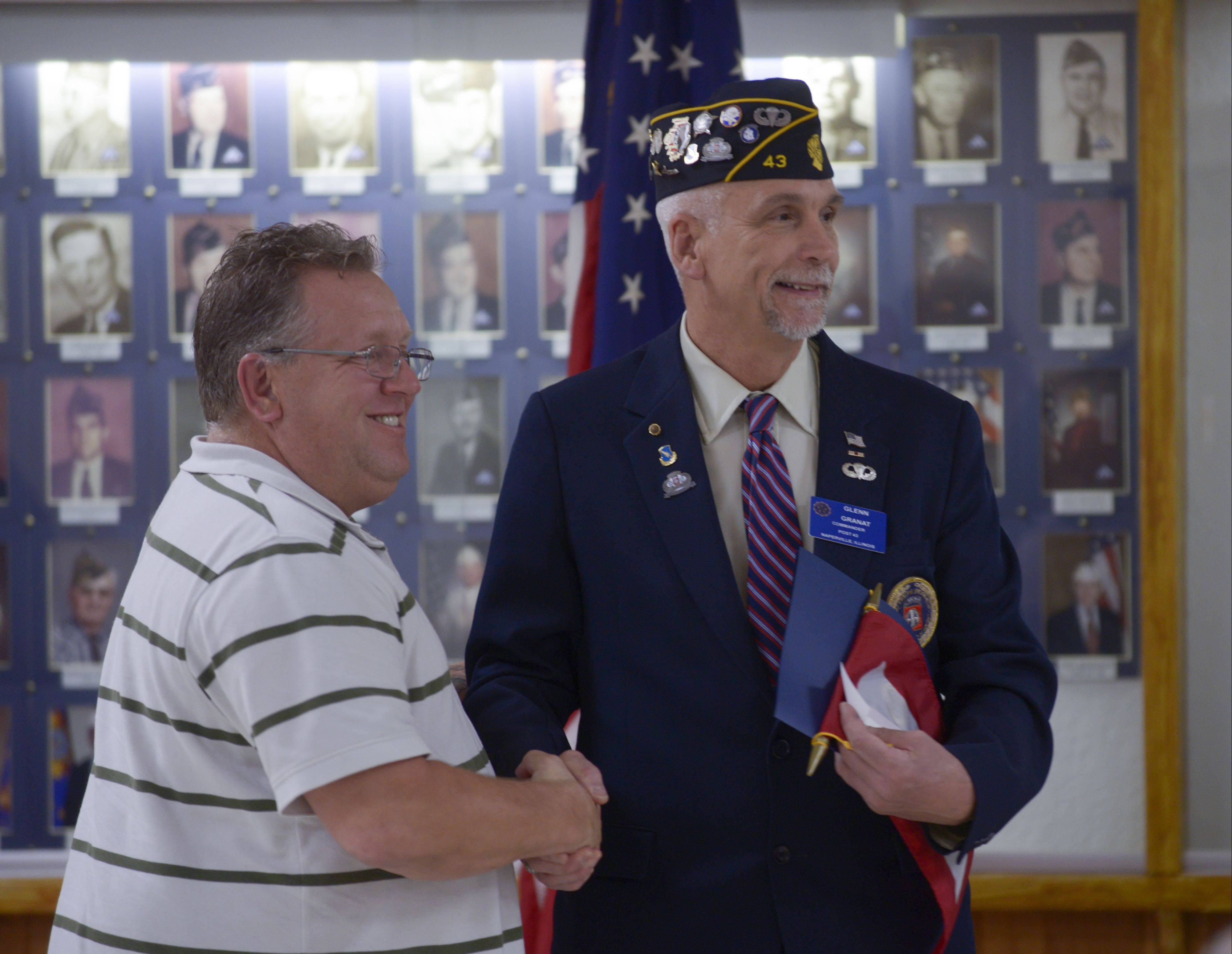 Greg Gennett of Medinah, whose son Greg is serving in the U.S. Marine Corps, receives a Blue Star Service Banner Sunday at VFW Post 3873 in Naperville from Glenn Granat of American Legion Post 43.