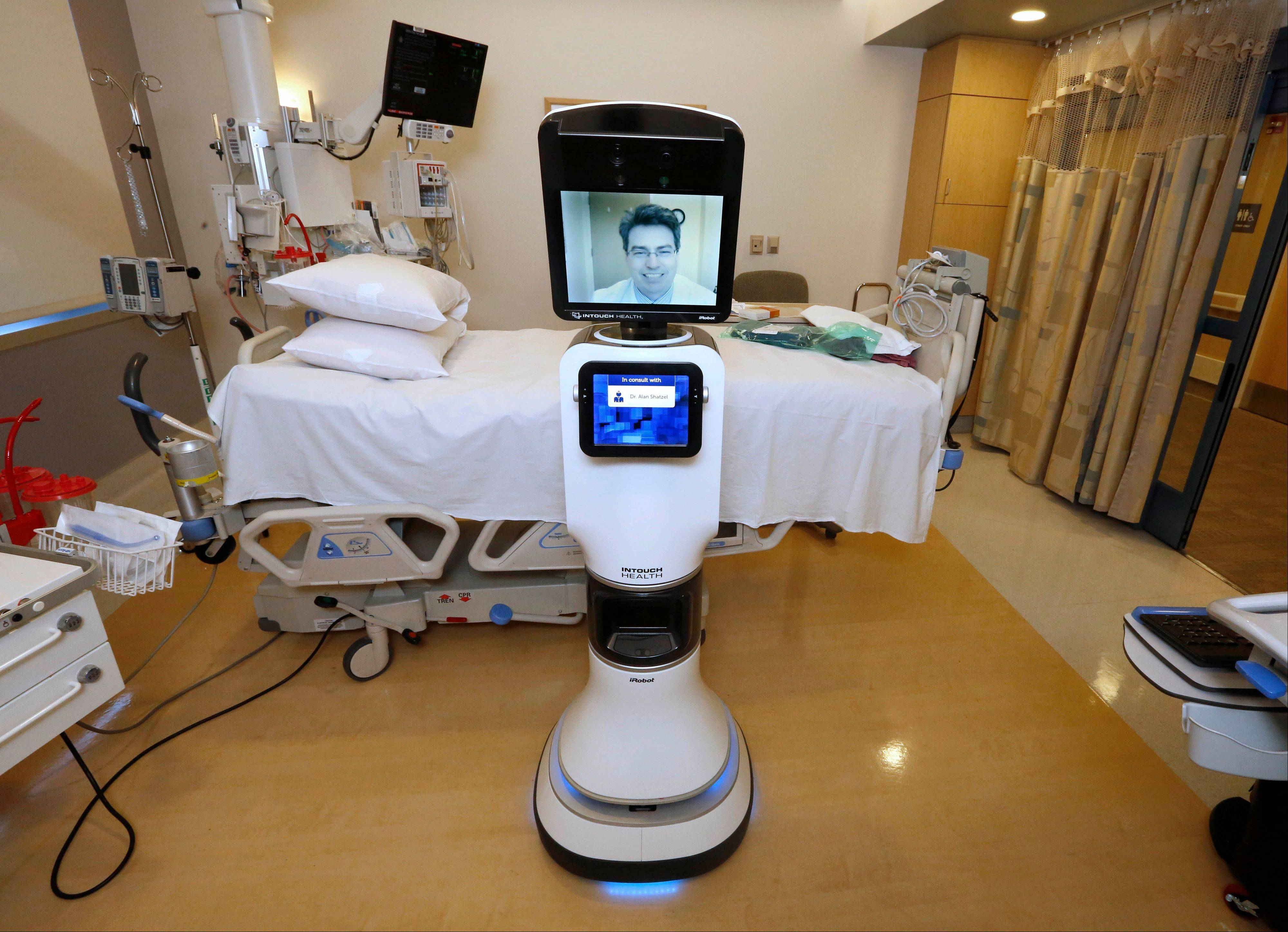 "Dr. Alan Shatzel, medical director of the Mercy Telehealth Network, is displayed on the monitor RP-VITA robot at Mercy San Juan Hospital in Carmichael, Calif. The robots enable physicians to have a different bedside presence as they ""beam"" themselves into hospitals to diagnose patients and offer medical advice during emergencies."