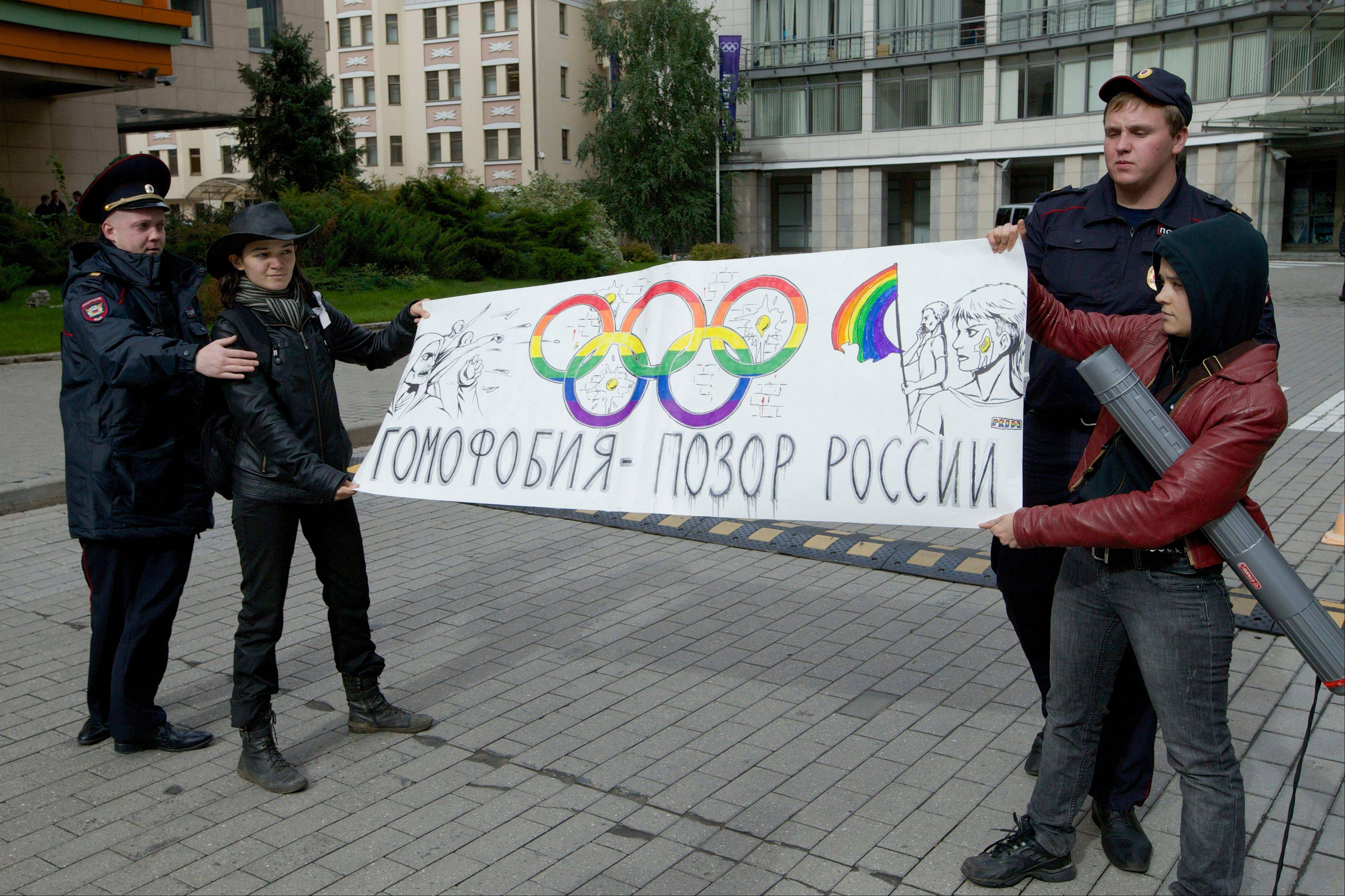 "Police officers detain two gay rights activists holding a poster reading ""Homophobia is Russia's Disgrace&q"