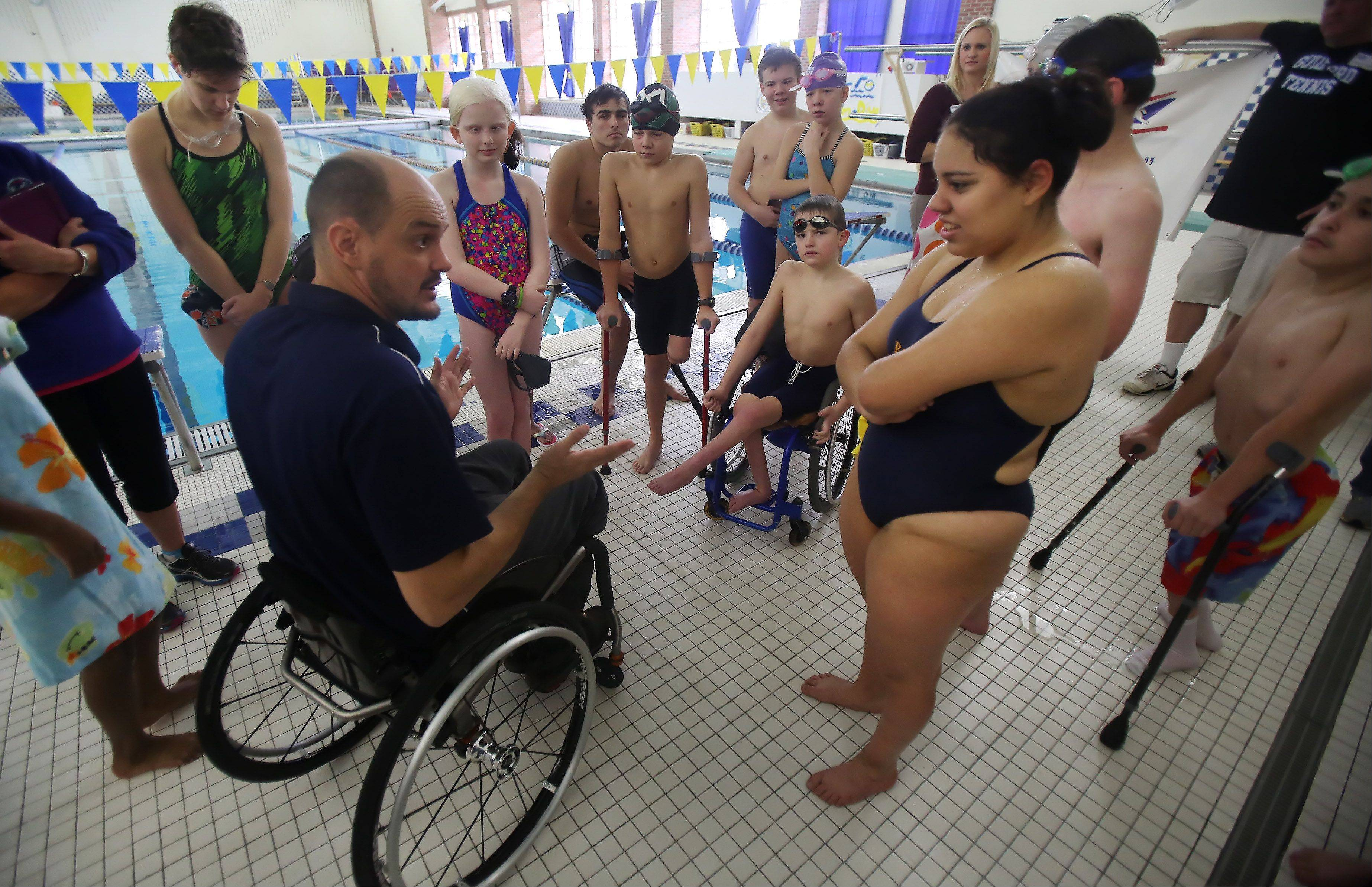 U.S. Paralympics swim coach Dave Denniston talks to children participating in the Gateway to Gold talent identification event Sunday at Lake Forest High School. The event was hosted by the Great Lakes Adaptive Sports Association to recognize individuals who could represent the country at the Paralympic Games.