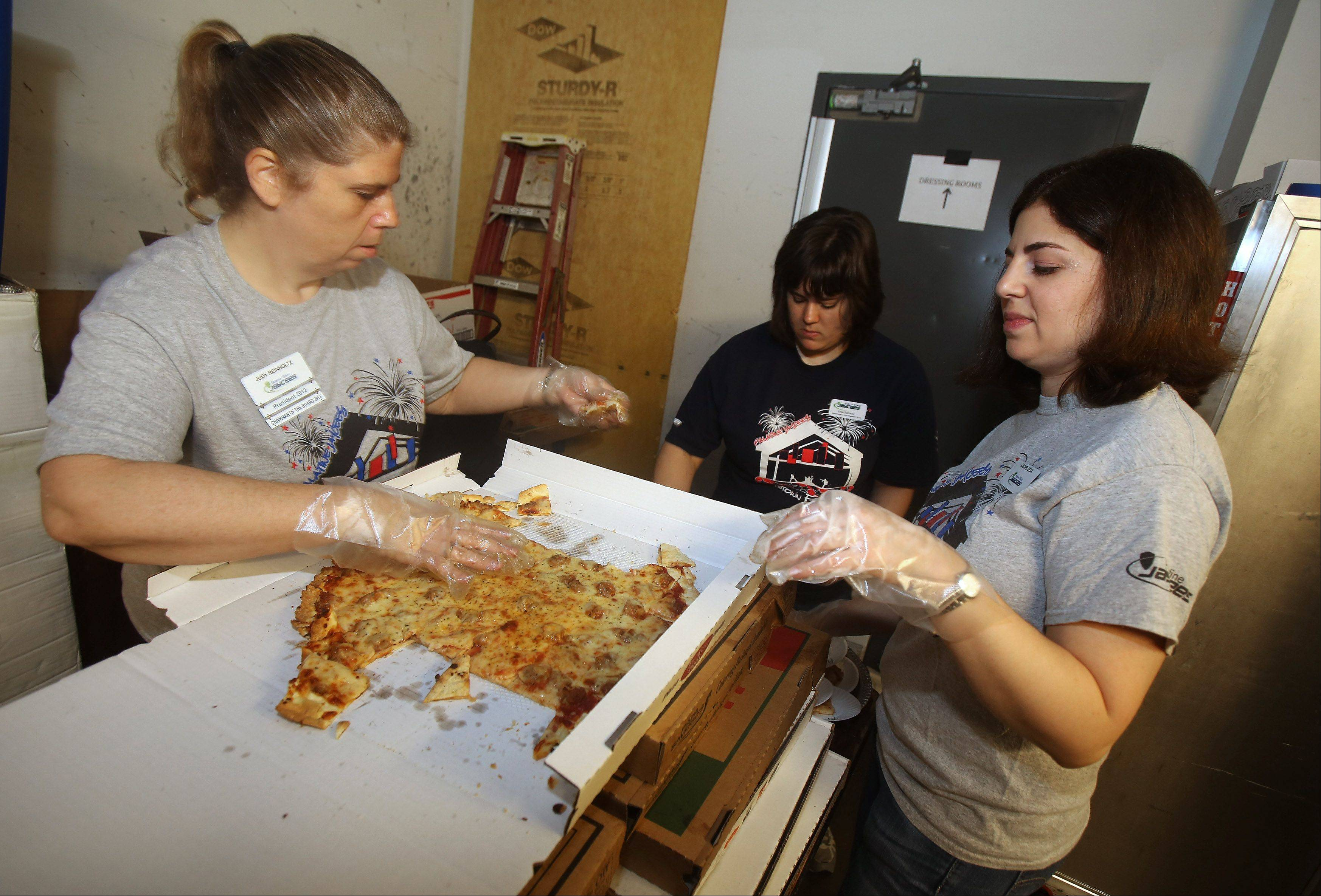 Palatine Jaycees Judy Reinholtz, left, Erika Bartnicki and Rachel Beck prepare pizza Sunday during the Palatine Jaycees Pizza Showdown at Durty Nellie's Bar and Grill. The Palatine Jaycees hold the annual contest to determine who makes the best pizza in the area. This year's winner was Vini's Pizza.