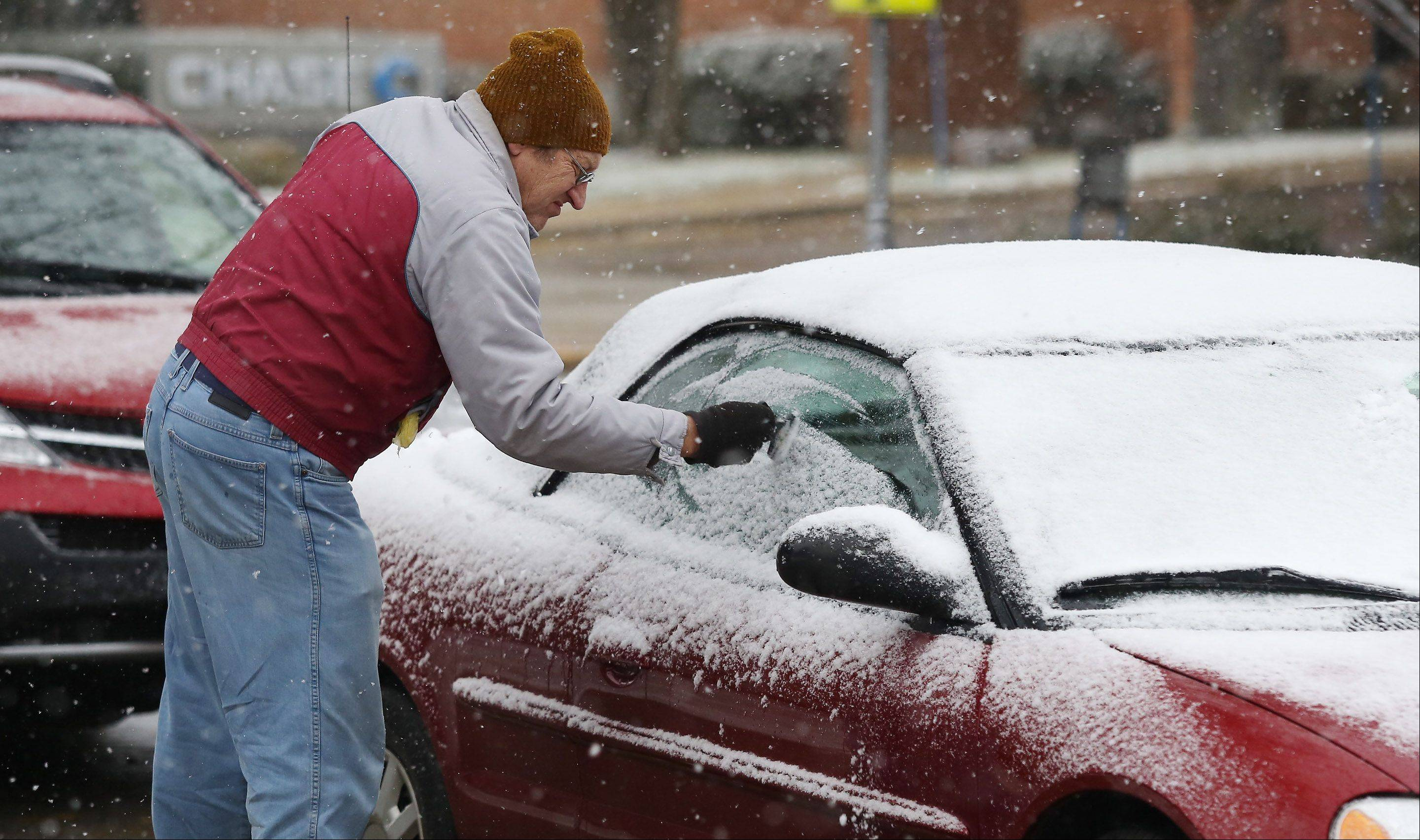 Paul Frisch, of Lake Forest, clears the snow from his car windows during the first snow fall of the season Monday near Cook Park in Libertyville.