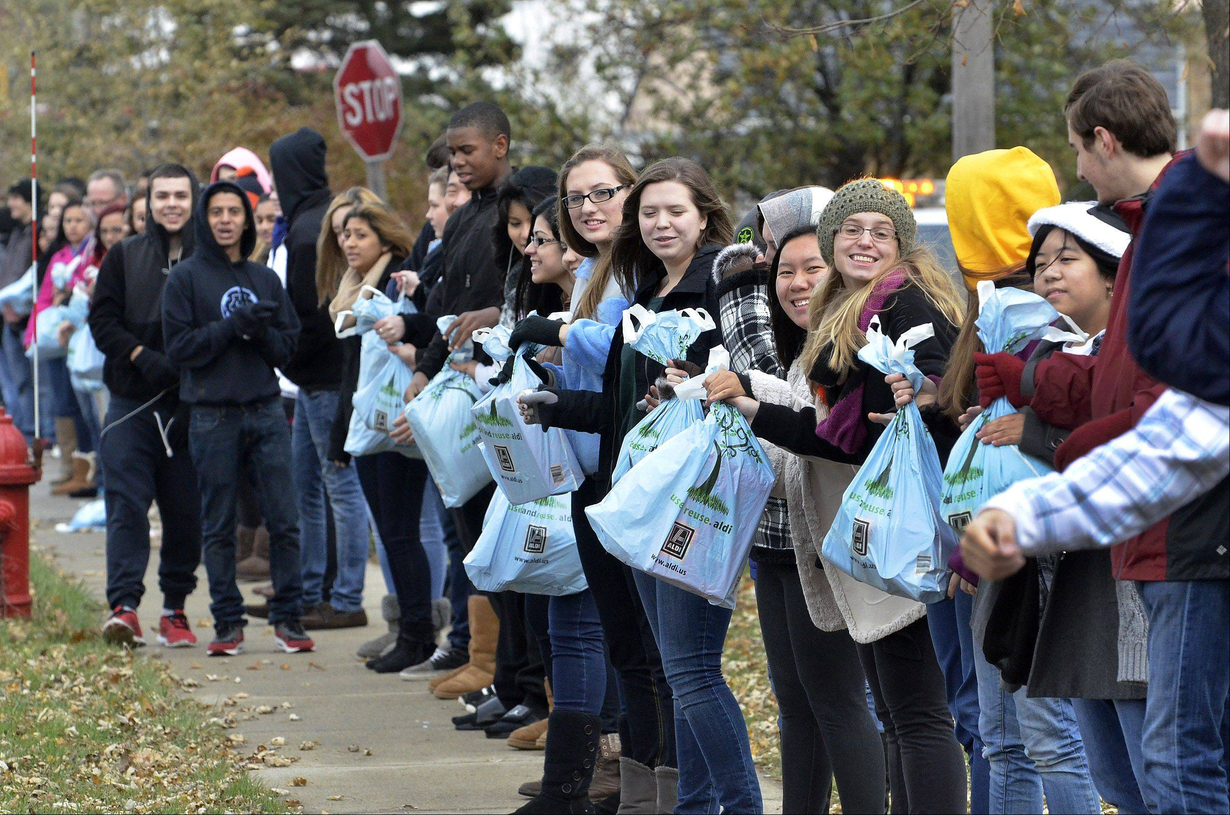 "For the 5th consecutive year, Maine West High School students and staff assembled a half-mile long human chain to help stock a Des Plaines food pantry on Algonquin and Wolf Roads. ""The students collected 7000 cans of food and toilet paper over the past week, and there are over 600 students and staff today participating in our Cans Across Des Plaines event,"" said student council sponsor Samantha Archer."