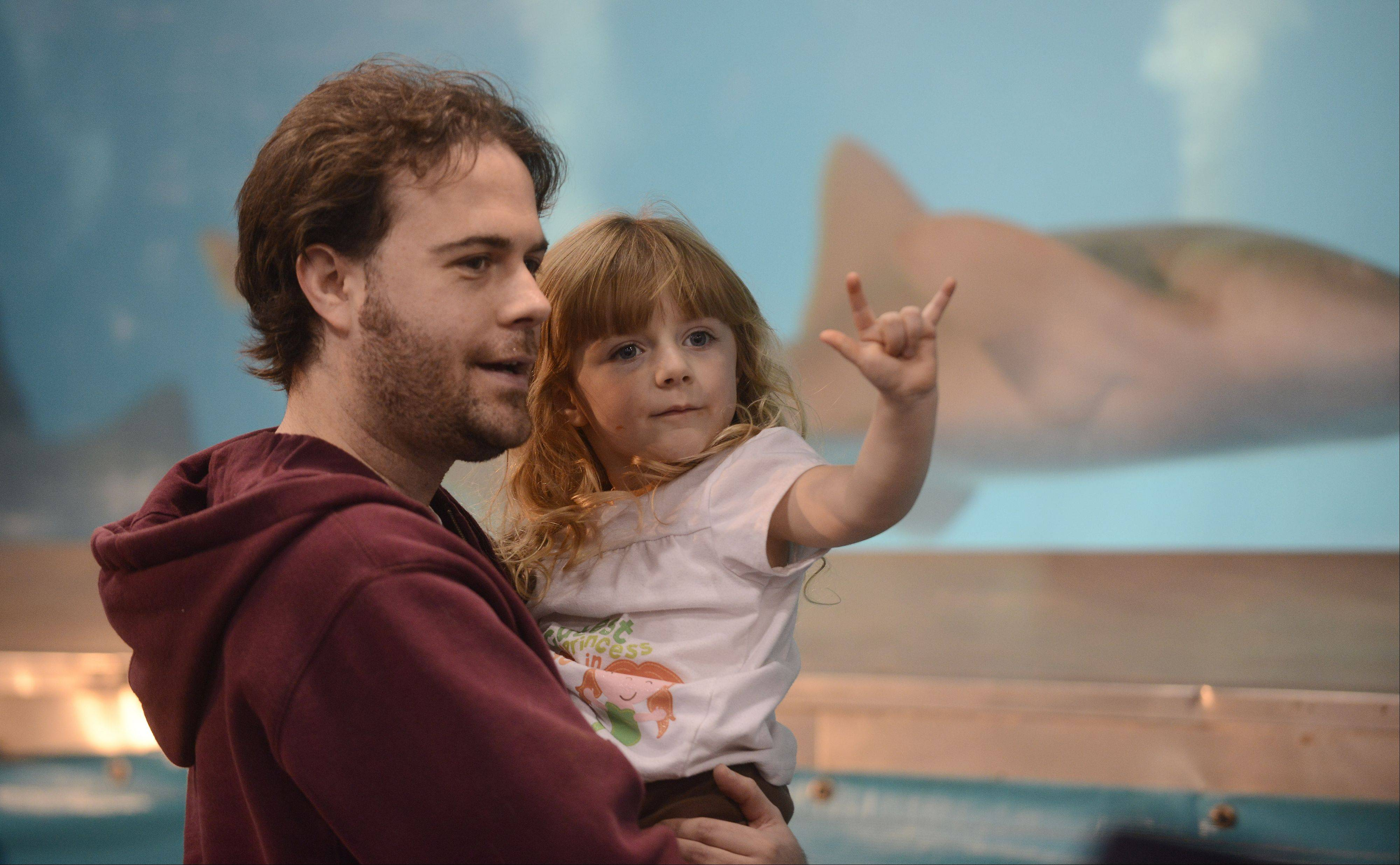 Jaymes Parker, of St. Charles, and his daughter, Lucinda, 3-1/2, view the shark tank during the Chicago Aquatic Experience Show, held at the Renaissance Schaumburg Convention Center Saturday.