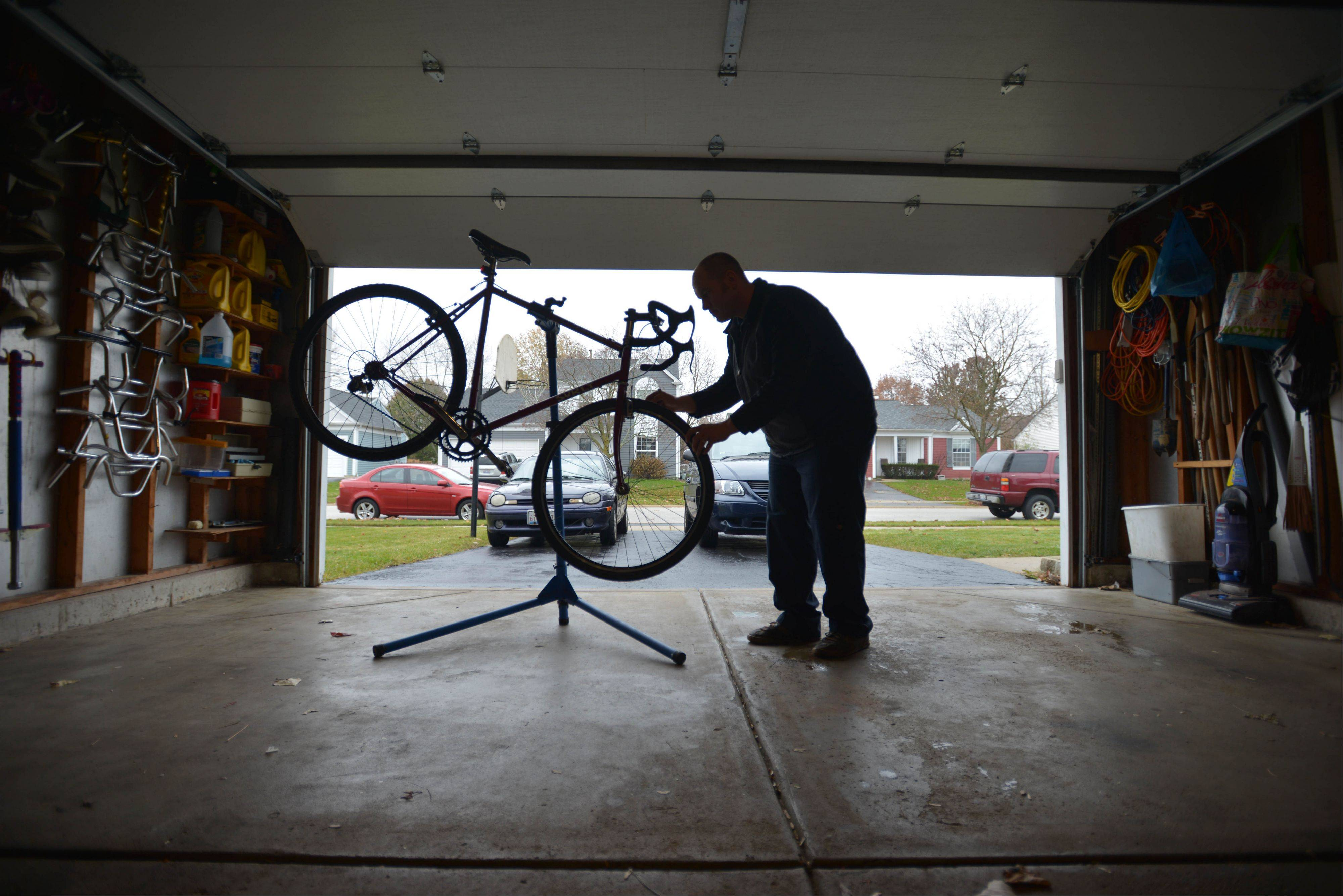 Brian Wroblewski, of Aurora, works on one of the six bikes in his garage Saturday afternoon. He was going to go for a ride, but it was raining.