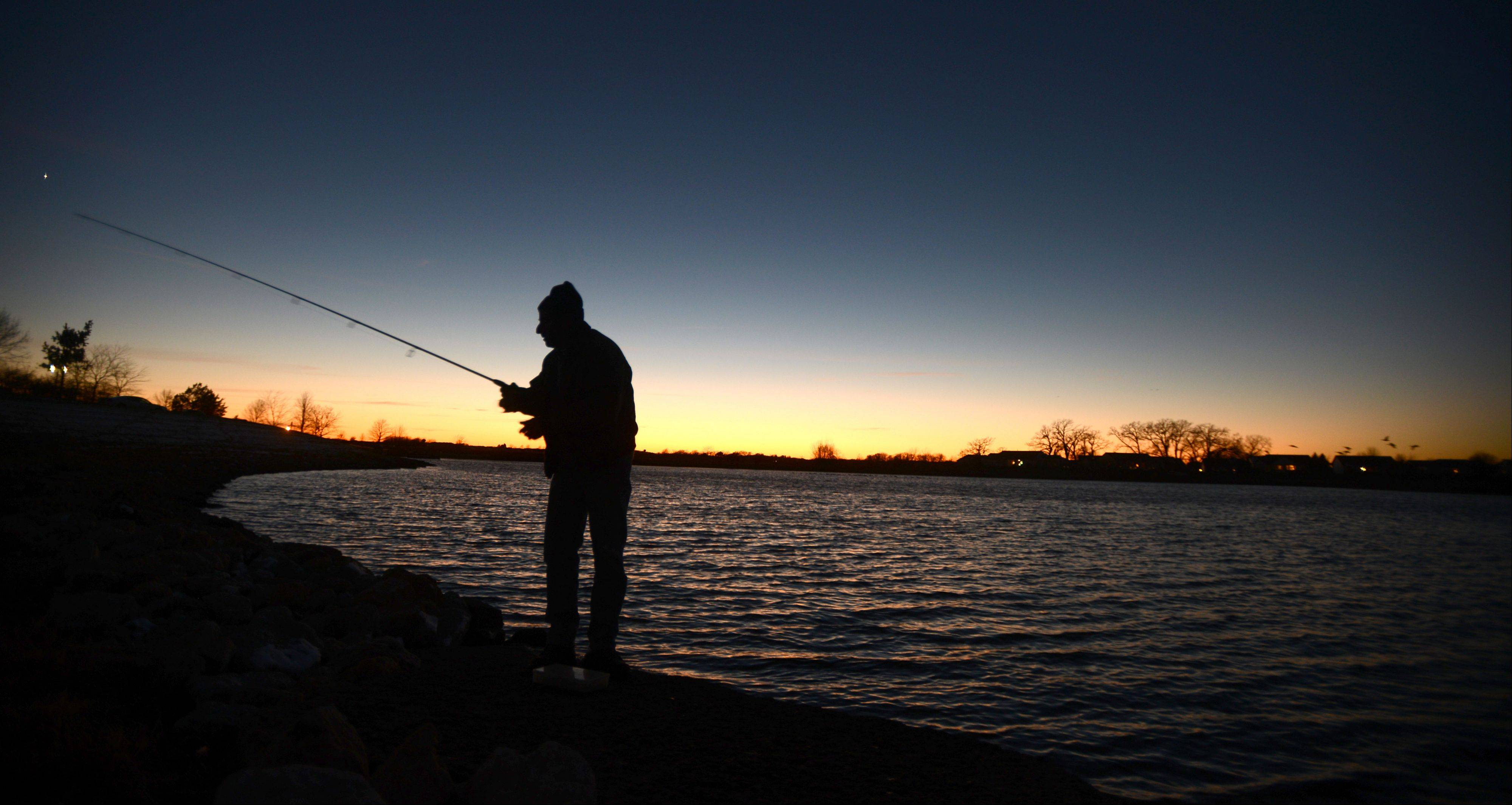 "Tony Bono, of Huntley, casts his line in the waters at Sun City Huntley at dusk on Wednesday. ""I am freezing and I haven't caught a thing,"" said Bono, ""Which is crazy because this is the time the big ones are biting."" Bono was hoping to catch a Northern or a Bass."