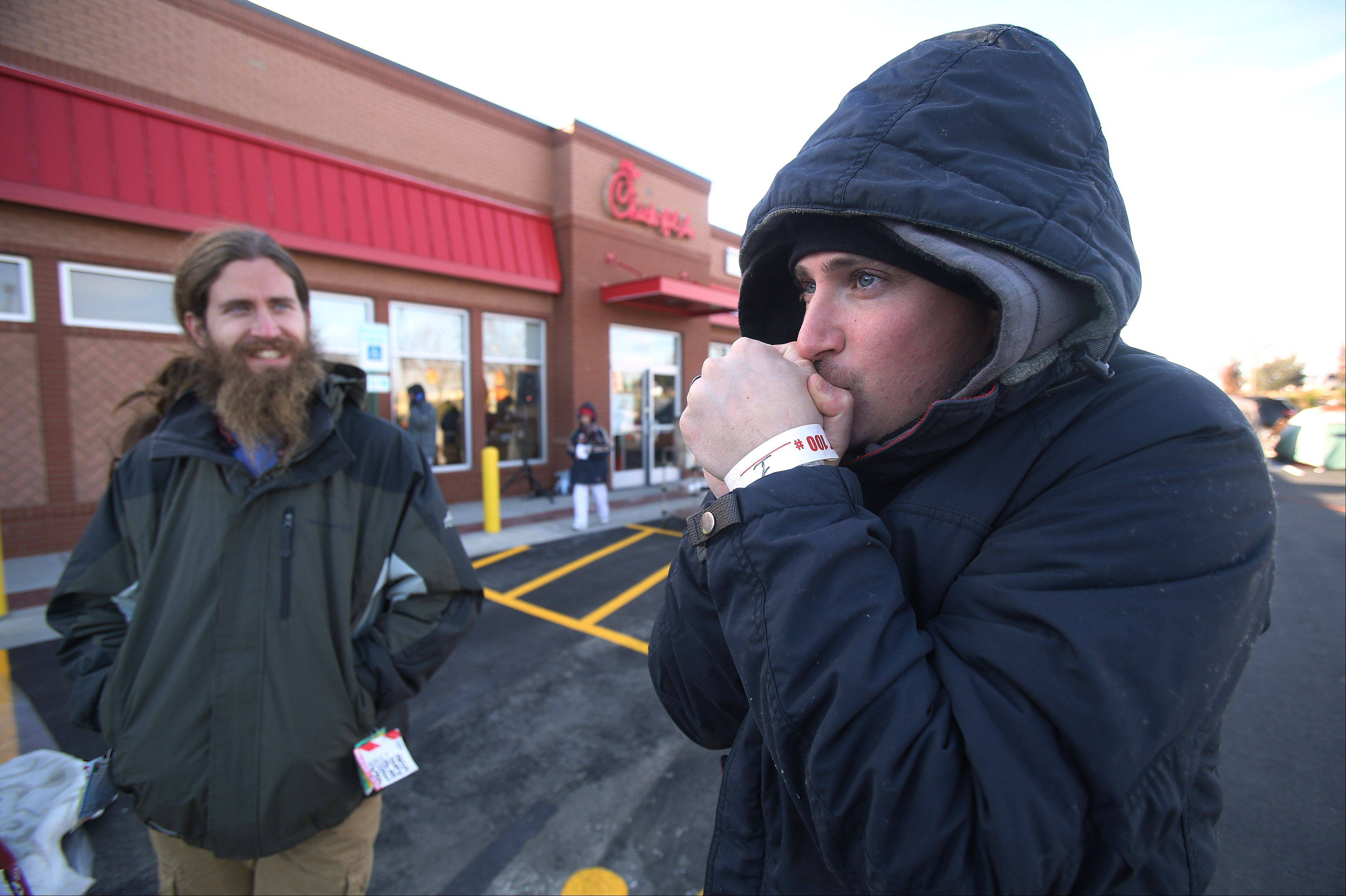 Jacob Schmanke, of Elgin, right, and his brother Josh, of Aurora, try to stay warm after being the first to stand in line Wednesday outside Chick-fil-A in Vernon Hills waiting for its grand opening on Thursday. They joined 100 people on a cold, blustery morning and will receive free meals for a year as part of a promotion by the restaurant chain.