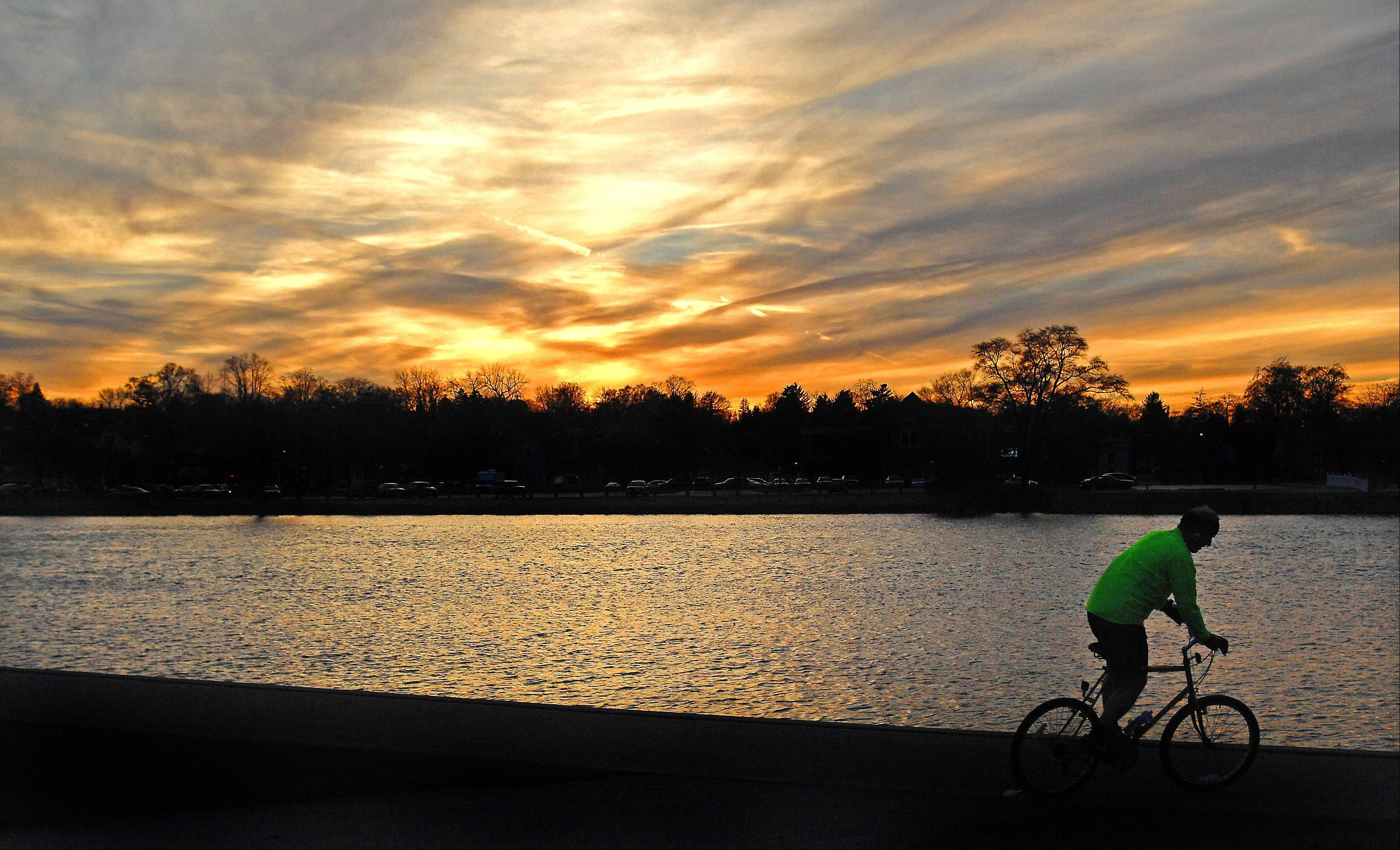 A bicyclist rides along the Fox River in St. Charles as the sun sets Thursday evening.