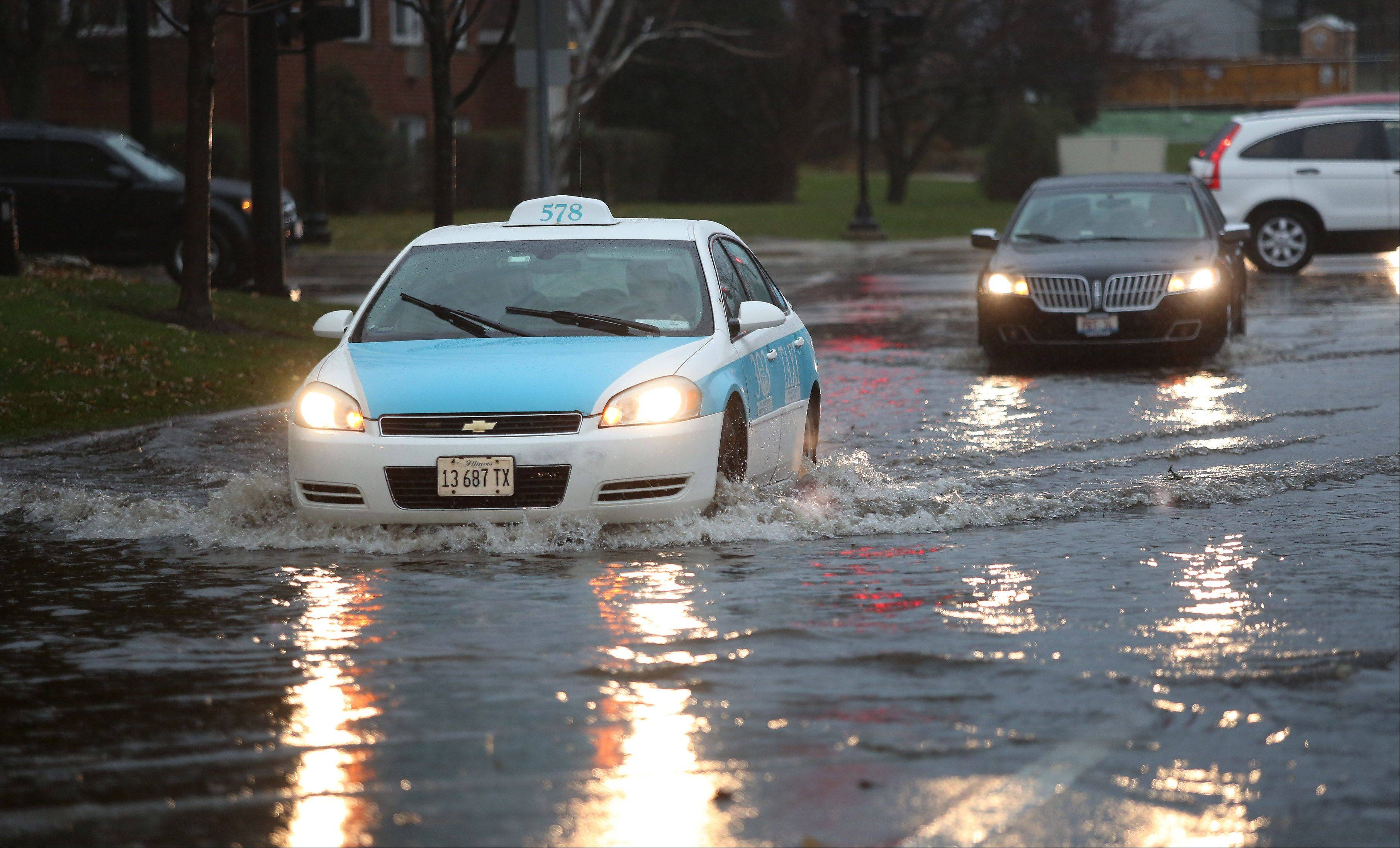 Cars drive through flooded streets at Smith Street and Colfax Street in Palatine as strong storms affected Chicago and the suburban area Sunday causing flooding problems and tornadoes to form south of Chicago. The Chicago Bears game at Soldier Field was delayed until the storms passed.