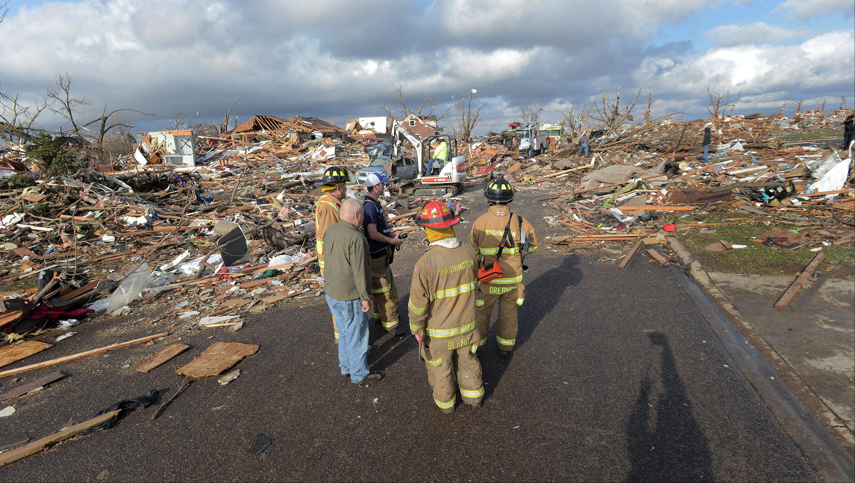 Washington, Ill., firefighters stand in the middle of Devonshire Street on the North side of Washington, Ill., after a tornado leveled at least fifty homes, Sunday, Nov. 17, 2013. High winds that followed the tornado are causing danger as homeowners and emergency workers try to search homes.