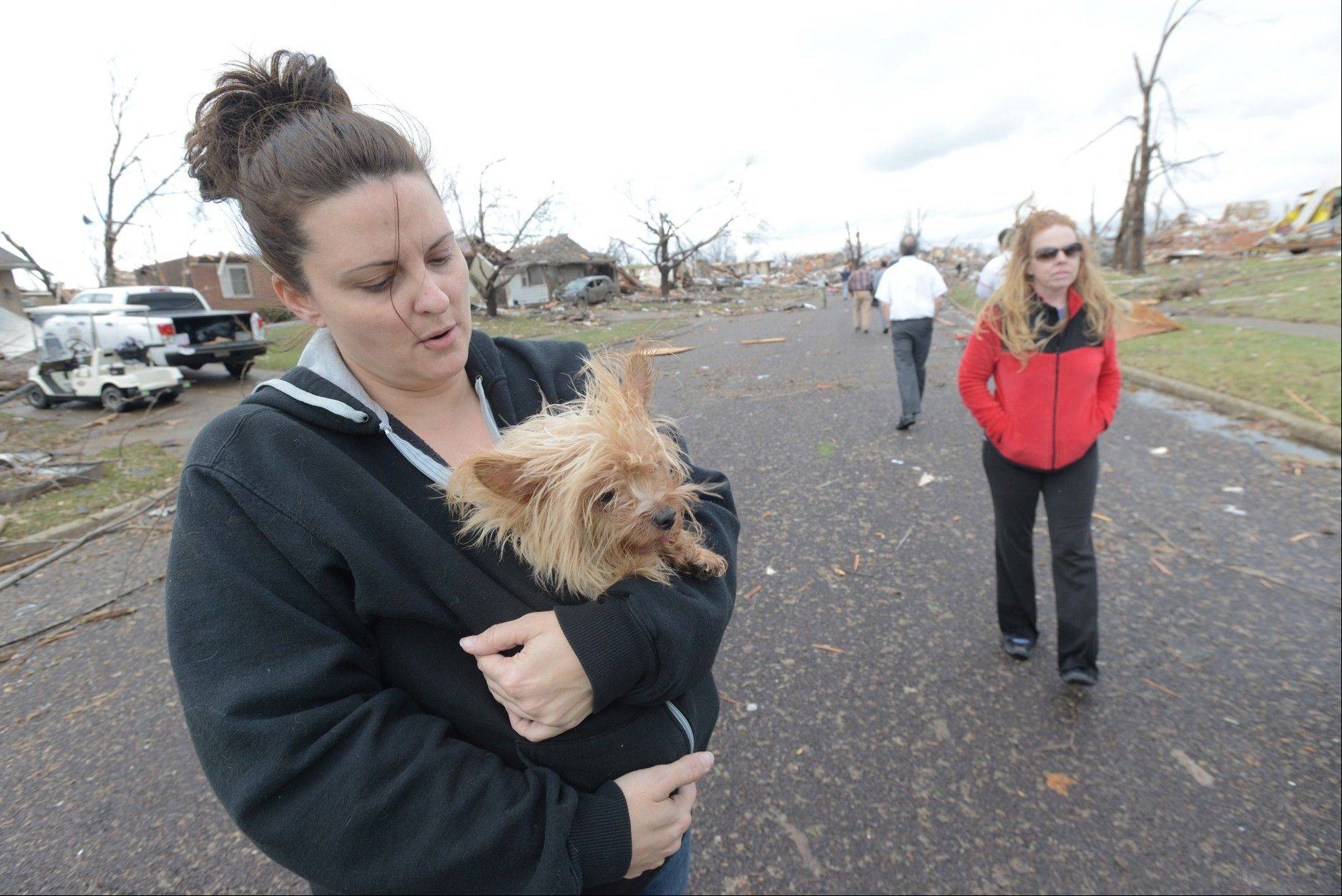 Aimee Royer holds a dog she rescued from debris after a Sunday morning tornado sliced through a subdivision on the North side of Washington, Ill., Sunday, Nov. 17, 2013. Royer and her friend, Kendra Gray, at right, said their home was spared. Several homes are cleared down to the foundation. Intense thunderstorms and tornadoes swept across the Midwest, causing extensive damage in several central Illinois communities while sending people to their basements for shelter.