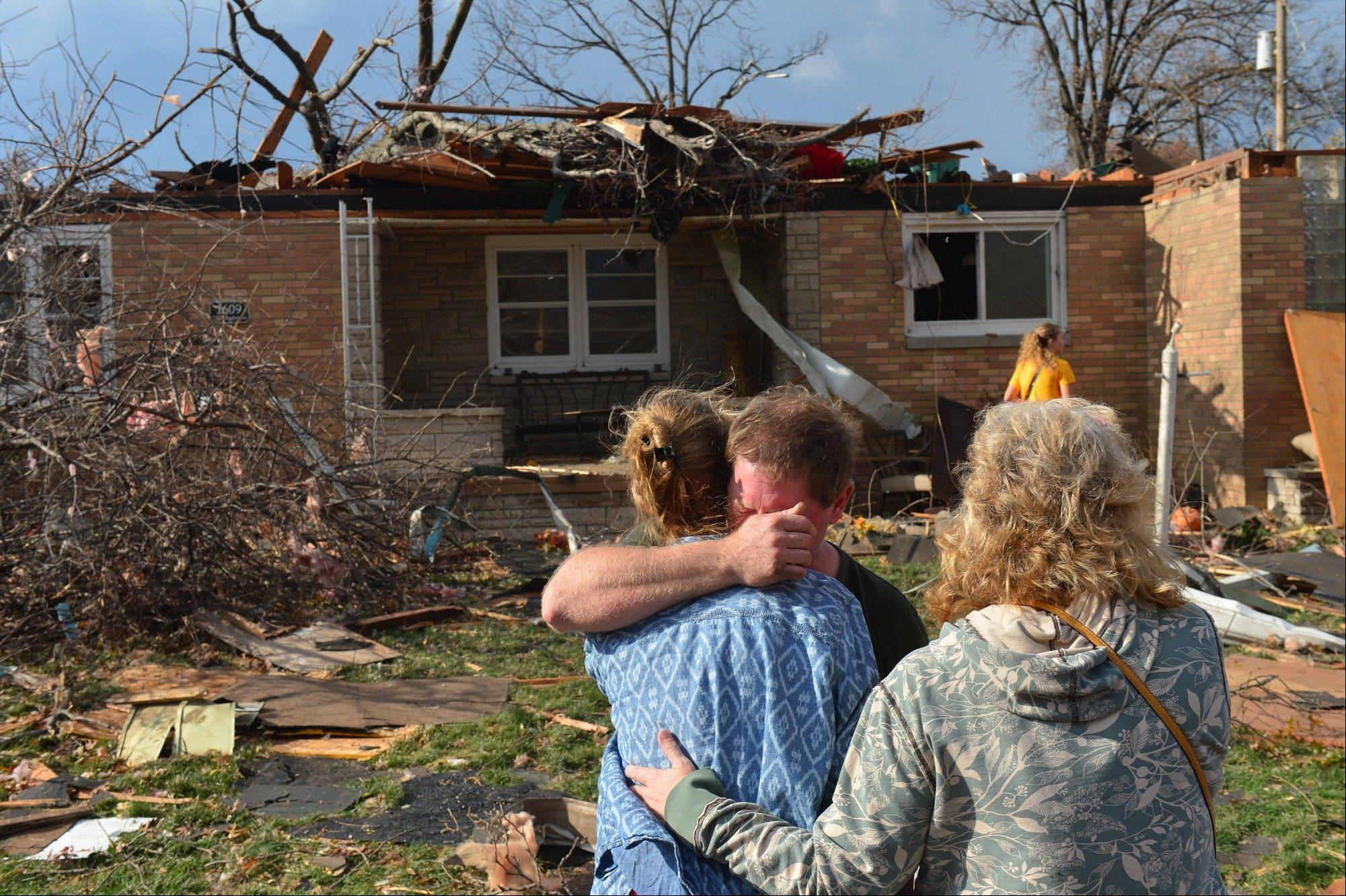 Ray Baughman embraces family shortly after his home was destroyed by a tornado that left a path of devastation through the north end of Pekin, Il., Sunday, Nov. 17, 2013. Intense thunderstorms and tornadoes swept across the Midwest on Sunday, causing extensive damage in several central Illinois communities while sending people to their basements for shelter.