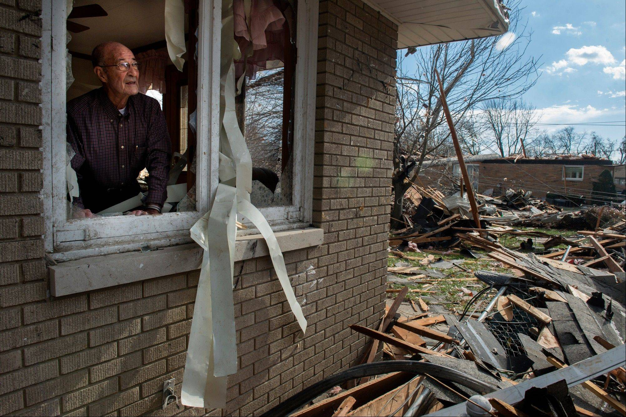 Chuck Phillips looks out at the destruction that tore off part of his roof and left houses around him destroyed after a tornado left a path of devastation through the north end of Pekin, Il., Sunday, Nov. 17, 2013. Intense thunderstorms and tornadoes swept across the Midwest on Sunday, causing extensive damage in several central Illinois communities while sending people to their basements for shelter.