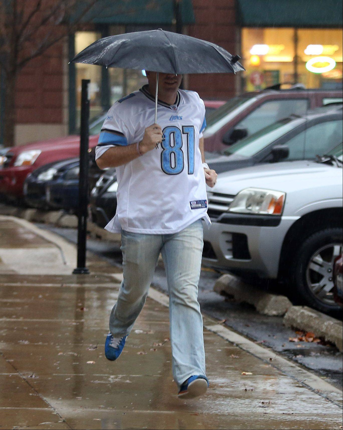 Tom Beebe of Palatine rushes to get out of the rain in downtown Palatine as strong storms affected Chicago and the suburban area Sunday causing streets to flood and tornadoes to form south of Chicago. The Chicago Bears game at Soldier Field was delayed until the storms passed.