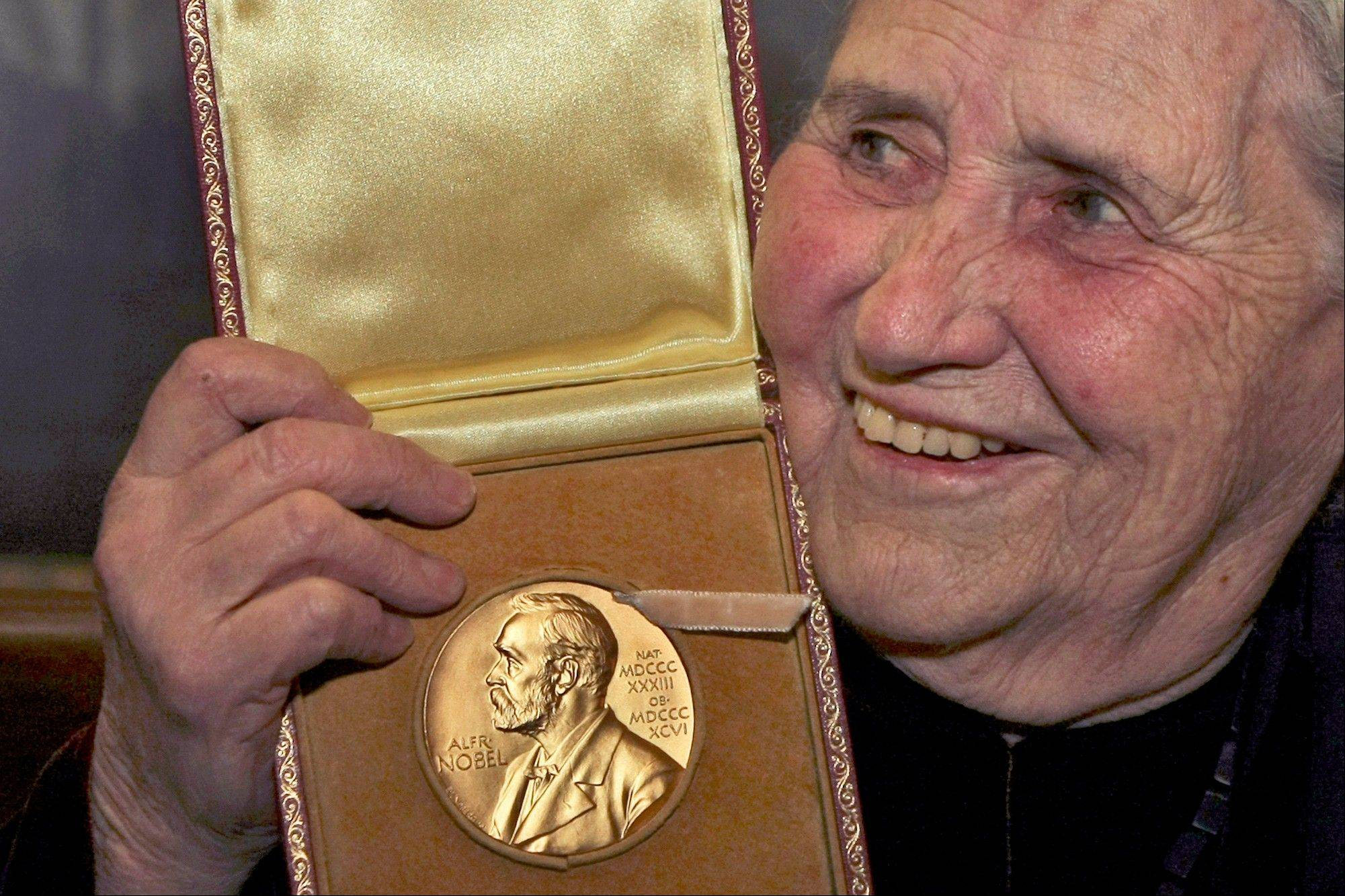 "In this Wednesday, Jan. 30, 2008 file photo, Nobel literature laureate, Doris Lessing holds up the 2007 Nobel Prize for Literature medal after being presented it by the Ambassador of Sweden, Staffan Carlsson, during a ceremony at the Wallace Collection art gallery in London. Doris Lessing, the free-thinking, world-traveling, often-polarizing writer of ""The Golden Notebook"" and dozens of other novels that reflected her own improbable journey across the former British empire, has died, early Sunday, Nov. 17, 2013. She was 94. The author of more than 50 works of fiction, nonfiction and poetry, Lessing explored topics ranging from colonial Africa to dystopian Britain, from the mystery of being female to the unknown worlds of science fiction."