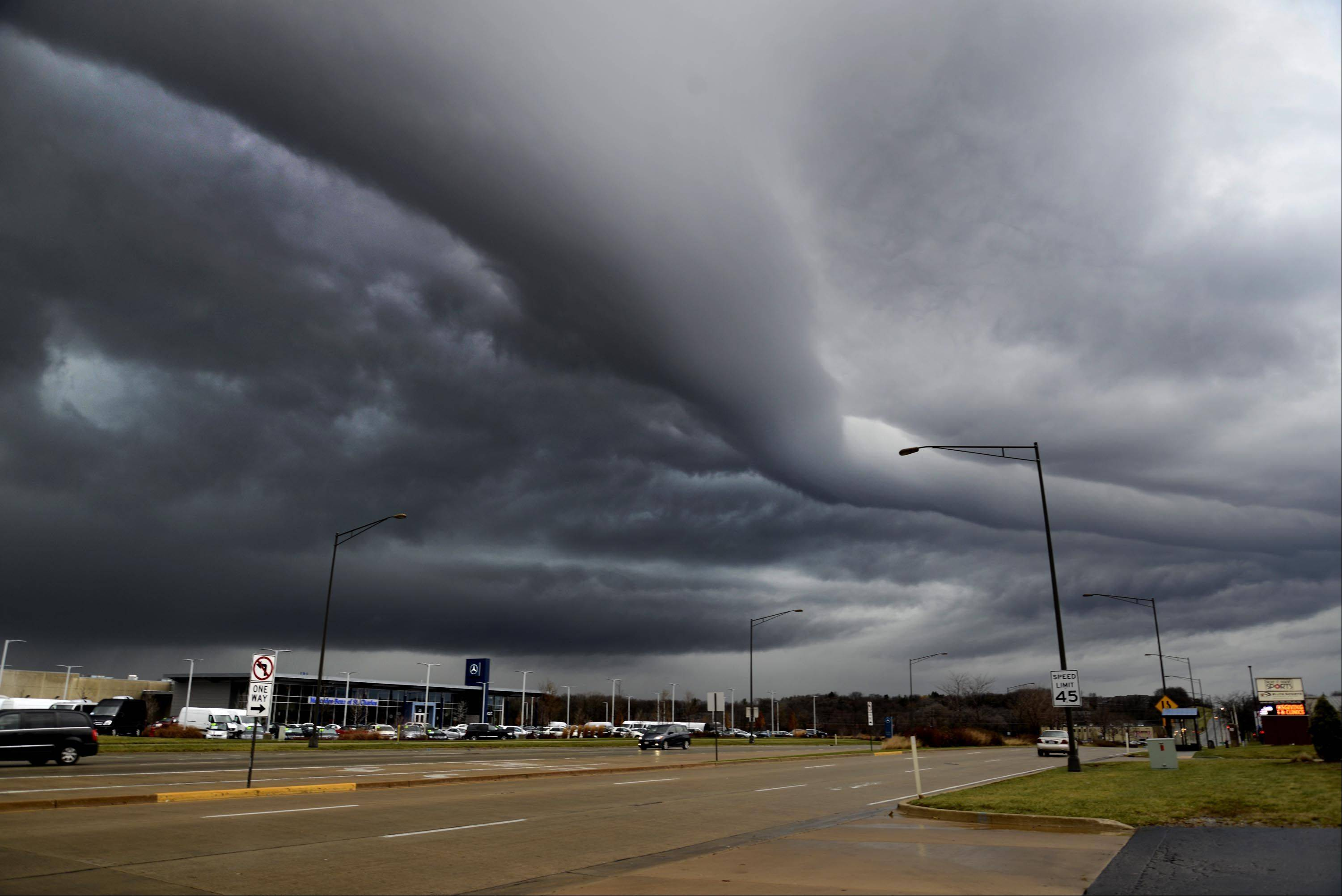 A front of clouds moves quickly over Randall Road from the west Sunday afternoon in St. Charles. Despite heavy rains and high winds, the Chicago area was spared the worst of the storms that tore through the Midwest on Sunday.