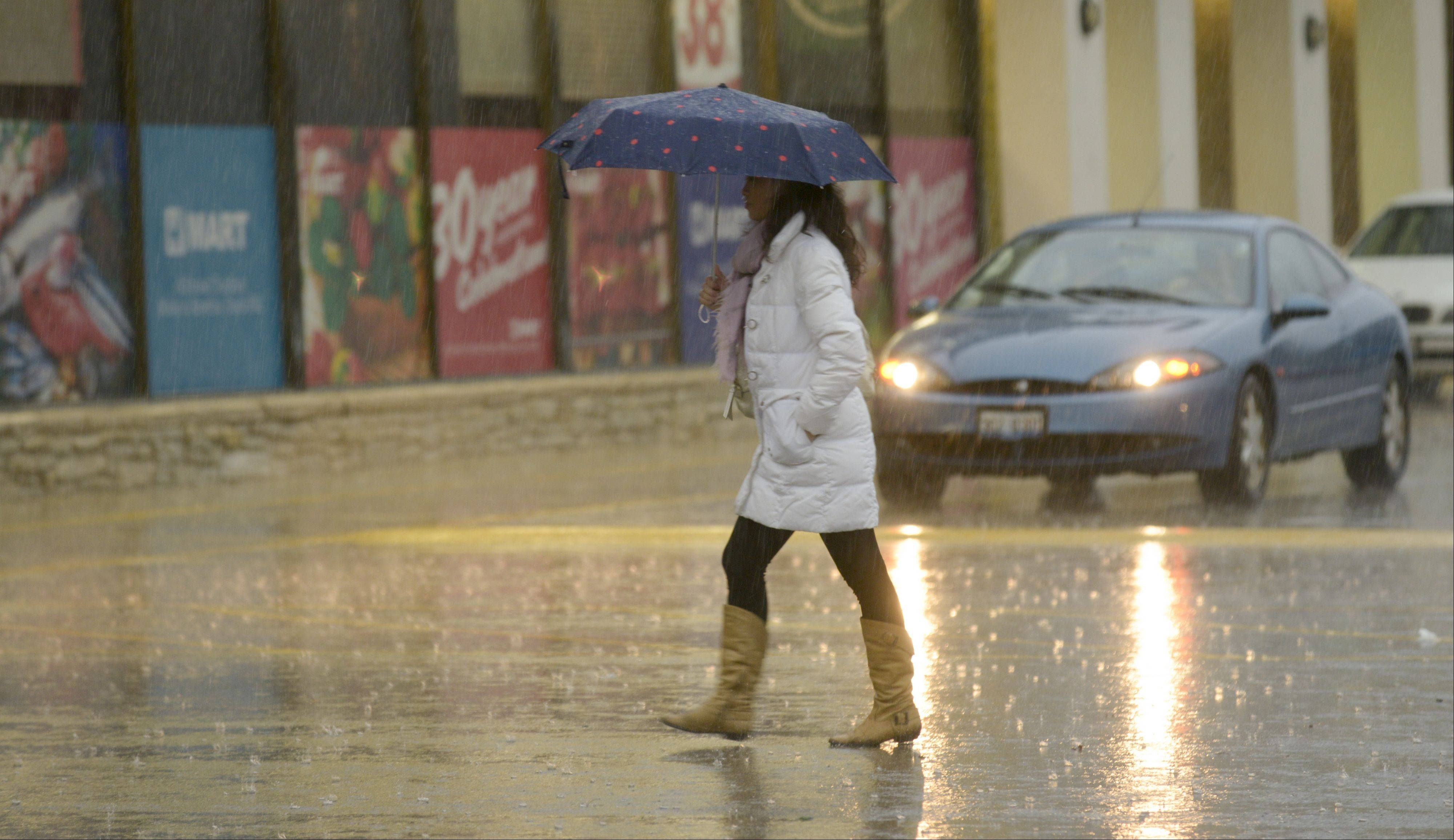 A shopper in Naperville uses an umbrella to keep from the heavy rains. Despite the downpour and high winds, the Chicago area was spared the worst of the storms that tore through the Midwest on Sunday.