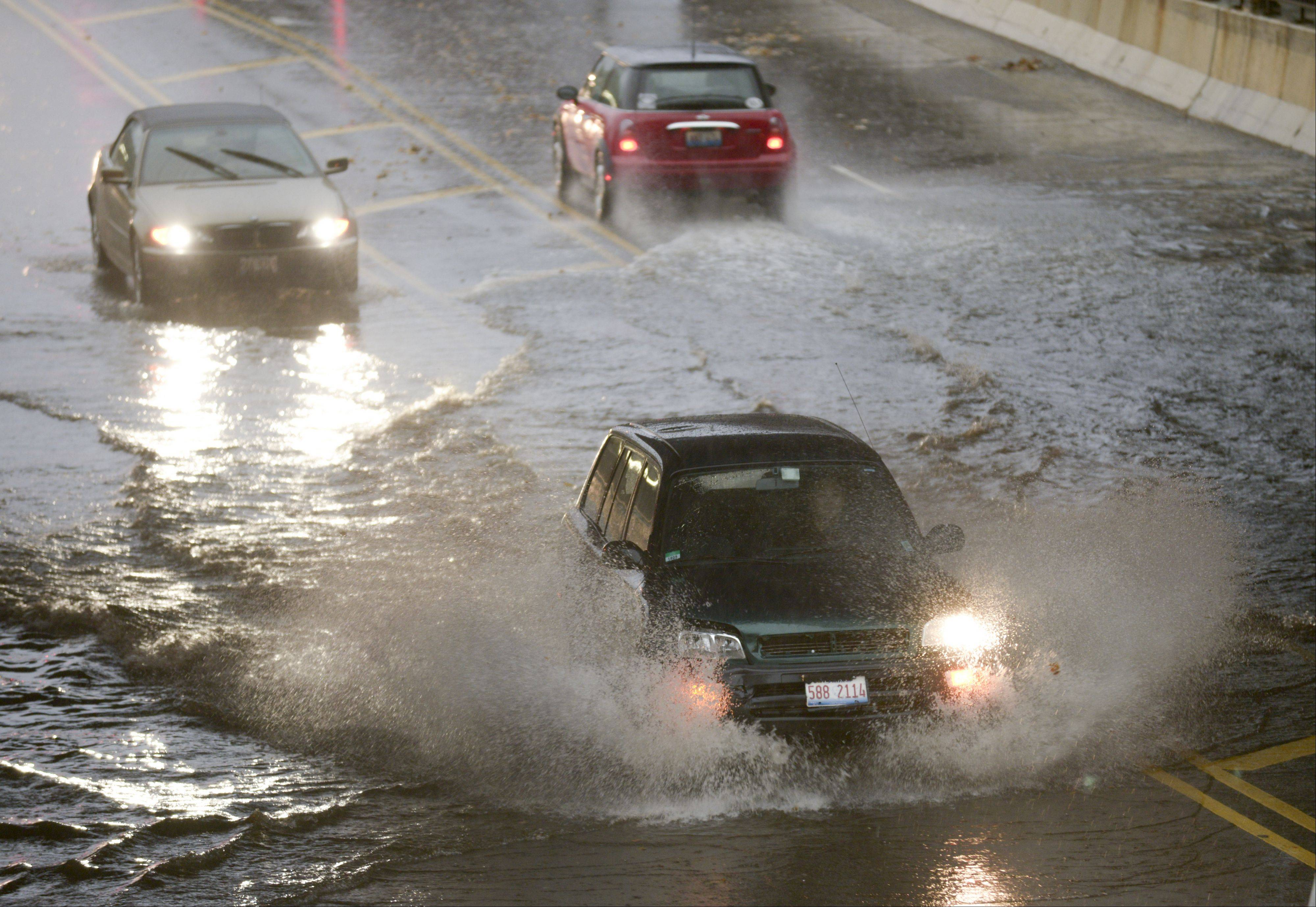 Cars slowly make their way through the flooded underpass on Washington Street under the railroad tracks in Naperville on Sunday. Despite heavy rains and high winds, the Chicago area was spared the worst of the storms that tore through the Midwest on Sunday.