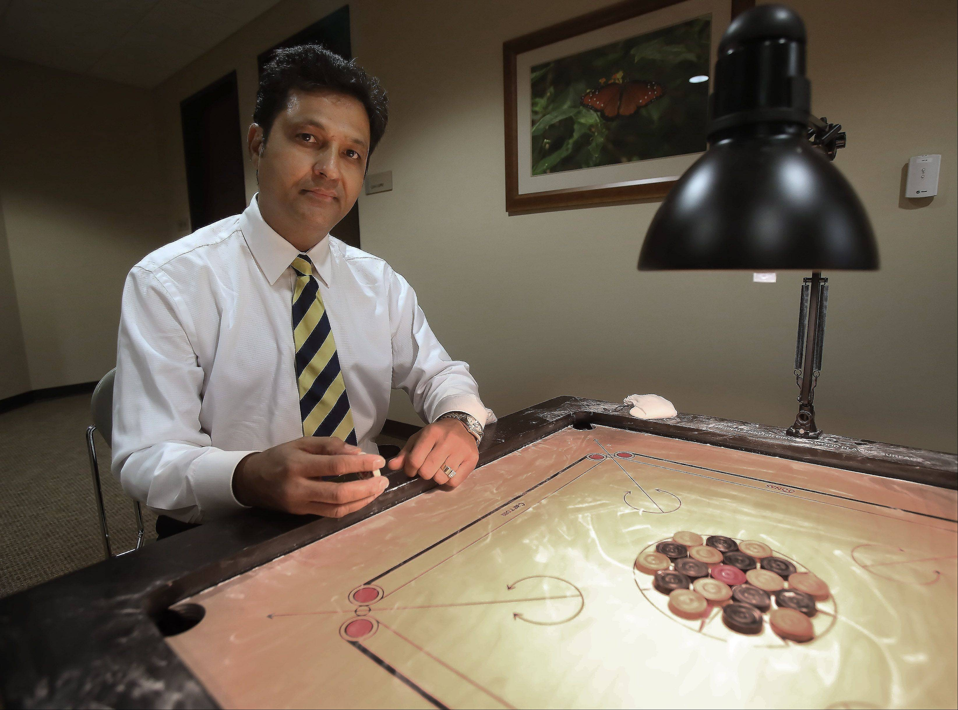 Vista Health oncologist Dr. Nilesh Mehta says the game of carrom is similar to pool. Mehta is vice president of the U.S. Carrom Association and a champion himself.