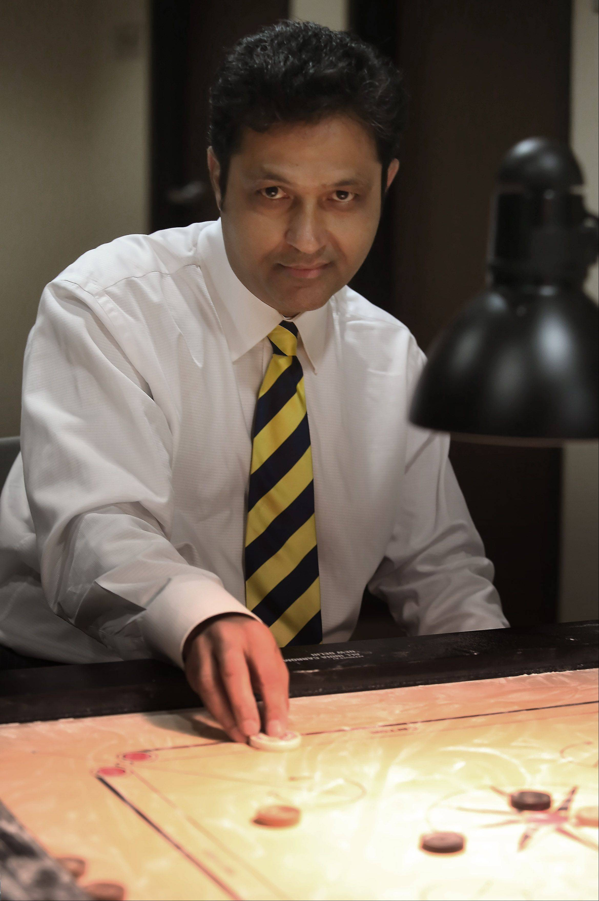 Vista Health oncologist Dr. Nilesh Mehta explains the game of carrom, which is similar to pool. Mehta recently won the national doubles championship during a national carrom tournament in Cleveland.