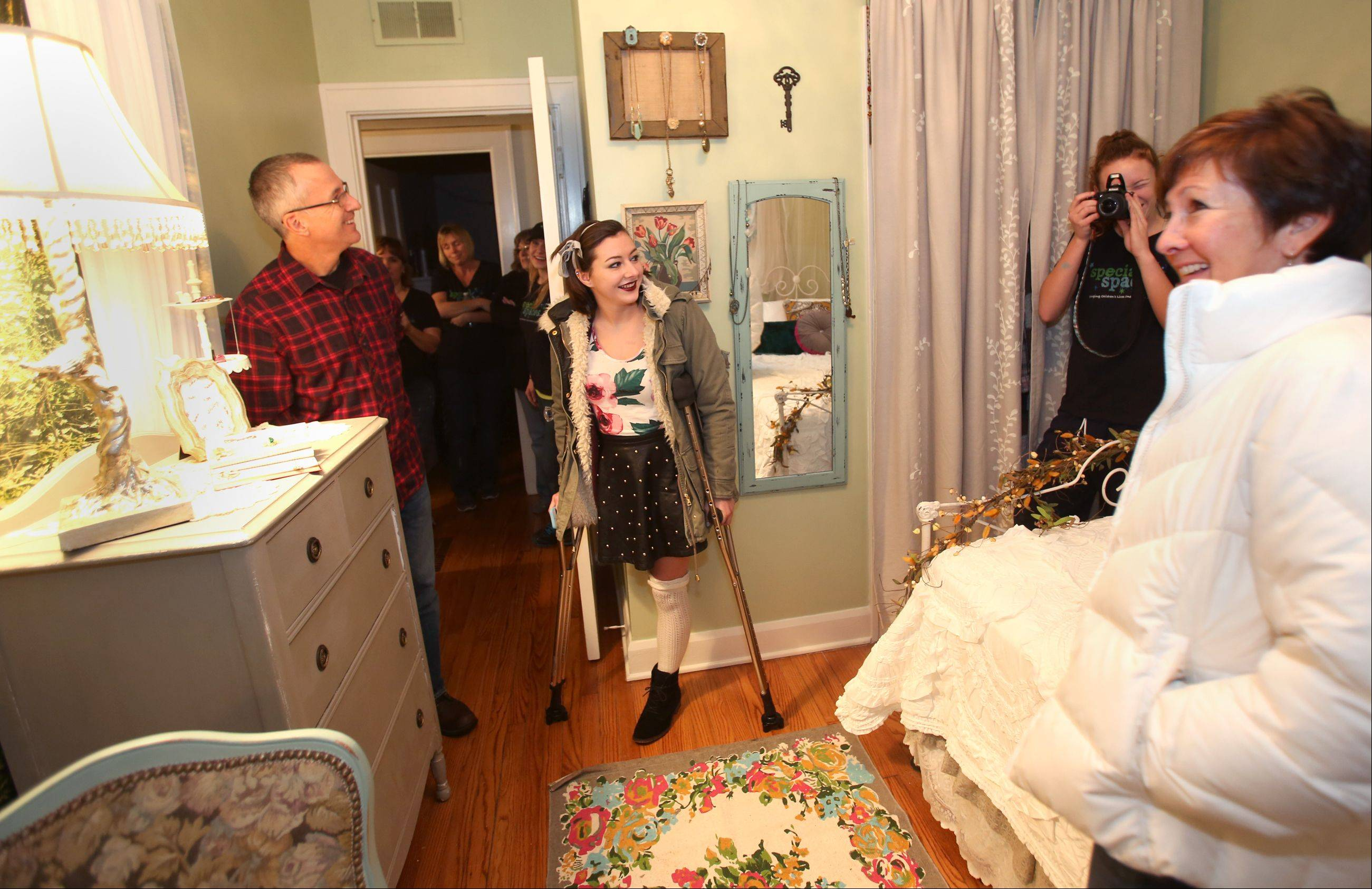 Genevieve Cipriano, 18, of Glen Ellyn looks over her bedroom with her parents Michael and Beth Cipriano. The room was designed by Special Spaces Chicagoland, a Naperville nonprofit organization that creates dream bedrooms for children with life threatening medical conditions.