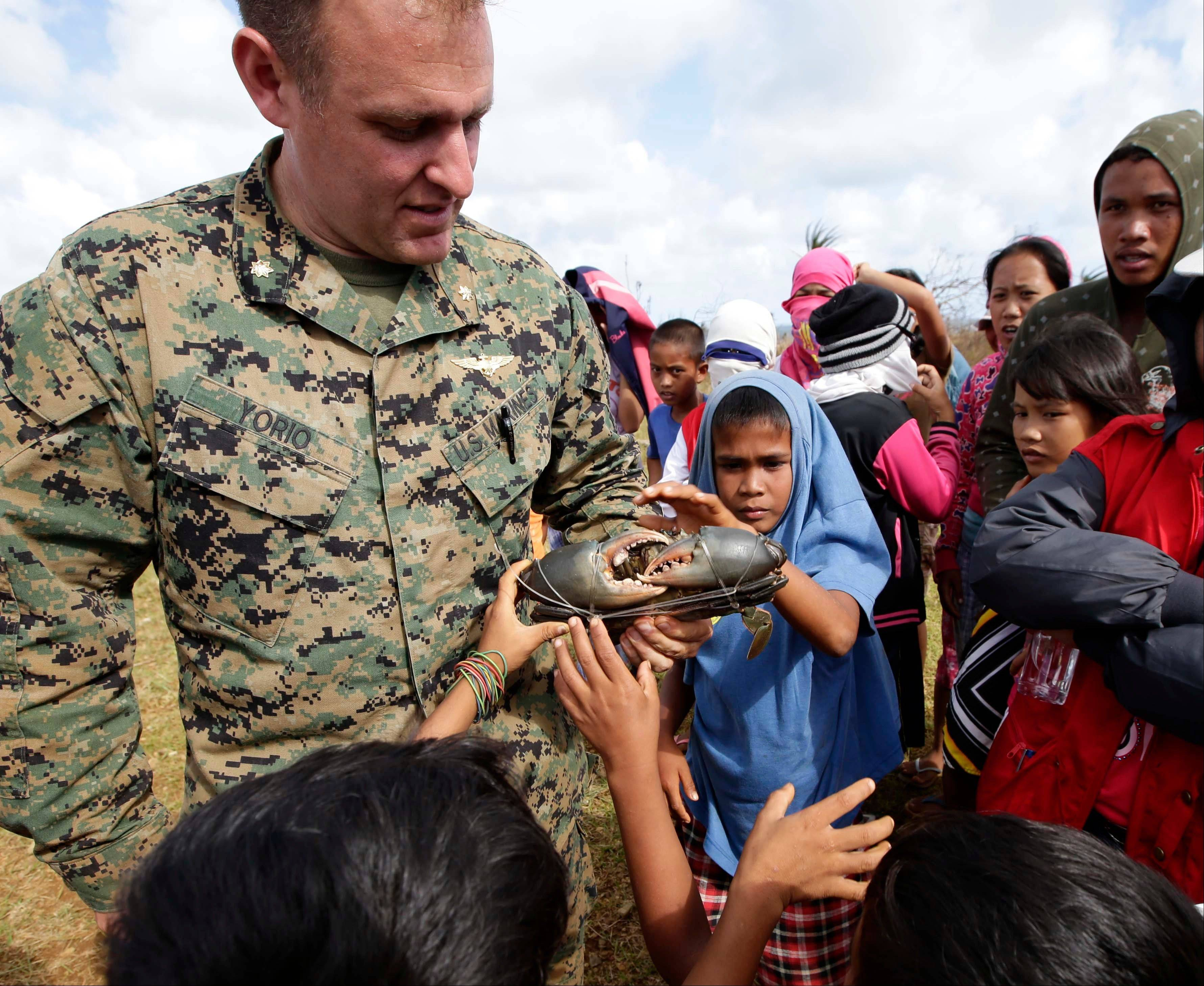 Marine Maj. John Orio examines a crab given to him Saturday by a resident in appreciation of the U.S. dropping off relief supplies on Manicani island, Eastern Samar province in central Philippines.