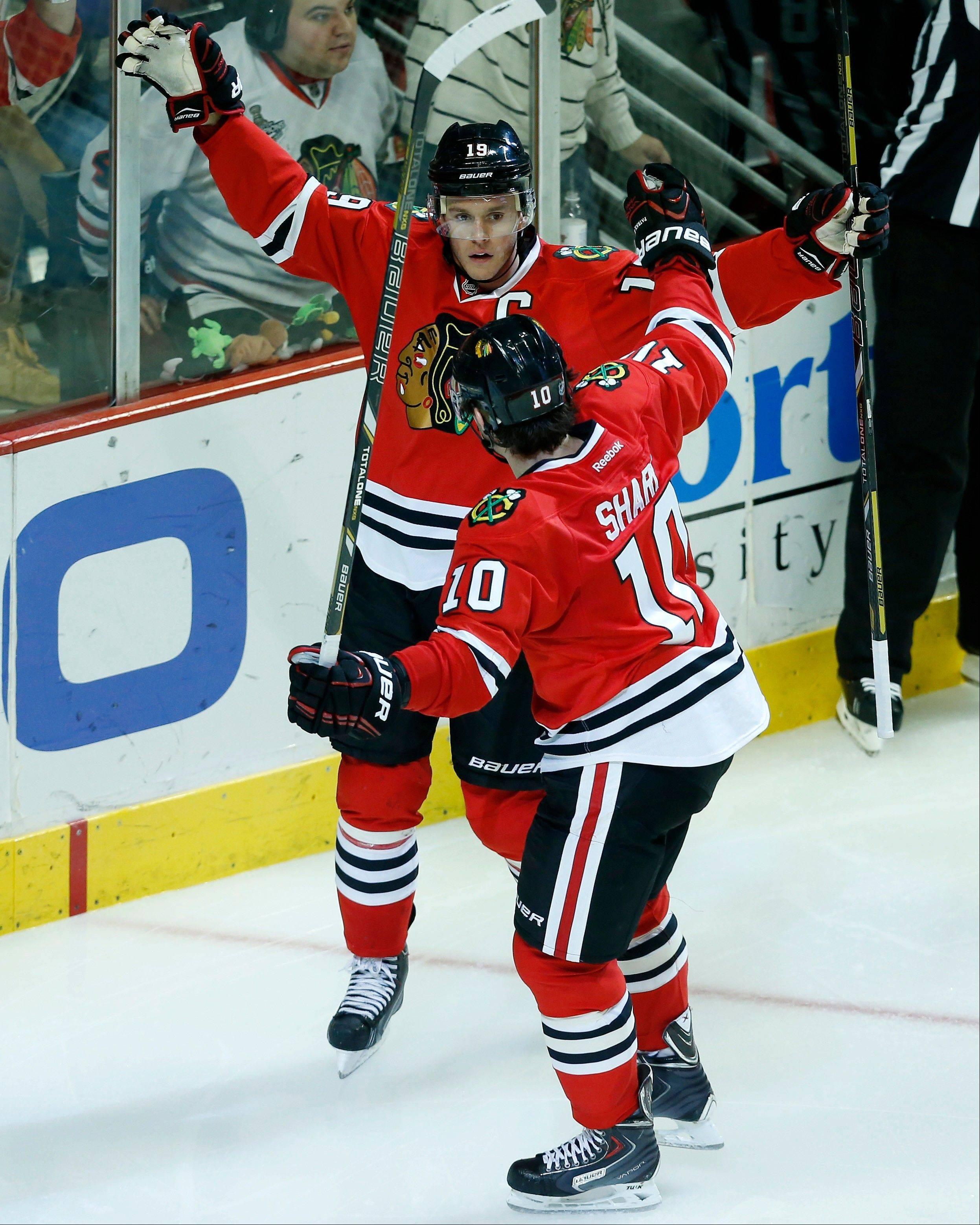 Jonathan Toews, back, celebrates with teammate left wing Patrick Sharp (10) after Toews scored a goal during the third period of an NHL hockey game against the San Jose Sharks on Sunday, Nov. 17, 2013, in Chicago.