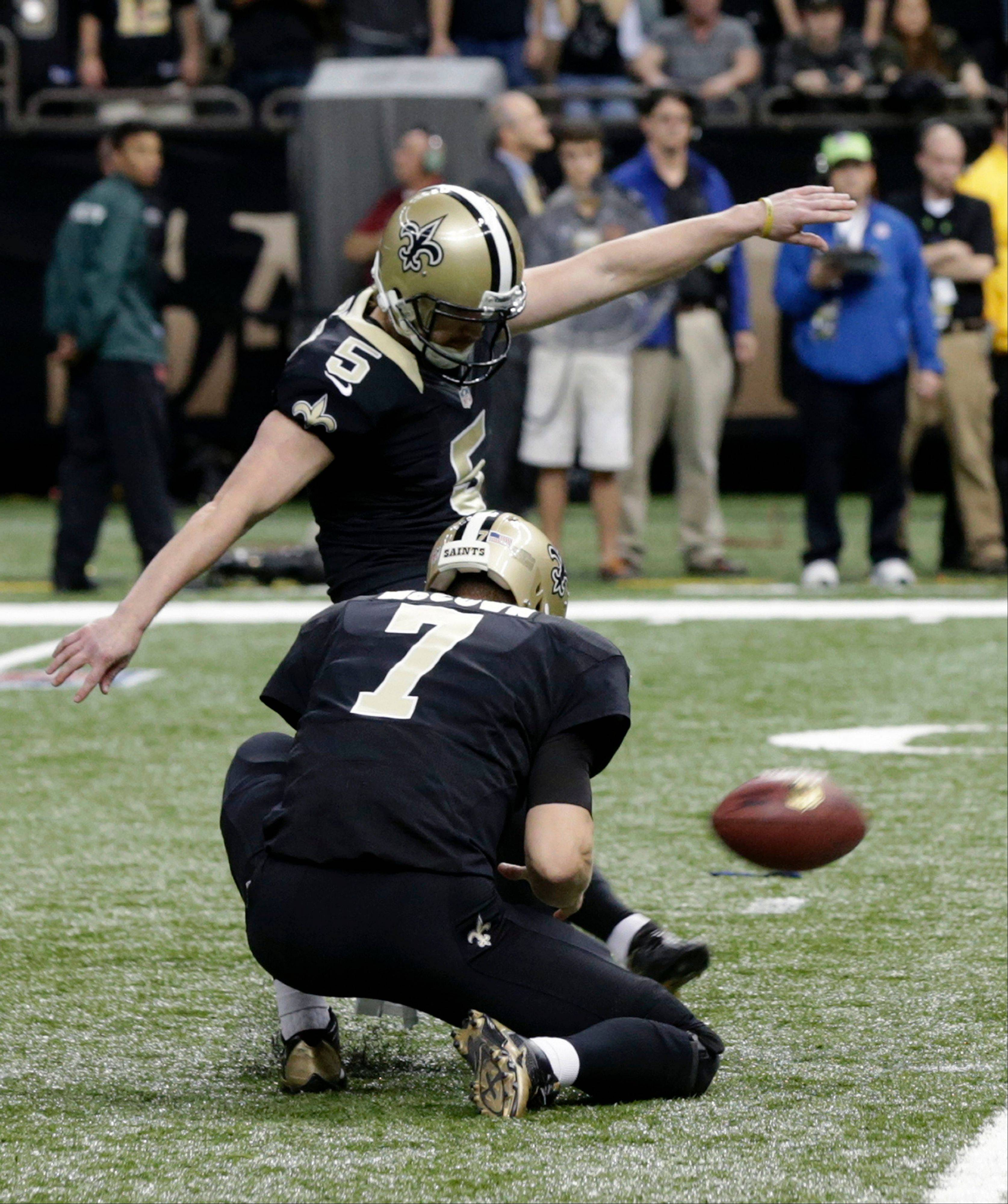 New Orleans Saints kicker Garrett Hartley (5) kicks the game winning field goal as Luke McCown holds at the end of regulation in the second half of an NFL football game against the San Francisco 49ers in New Orleans, Sunday, Nov. 17, 2013. The Saints won 23-20.