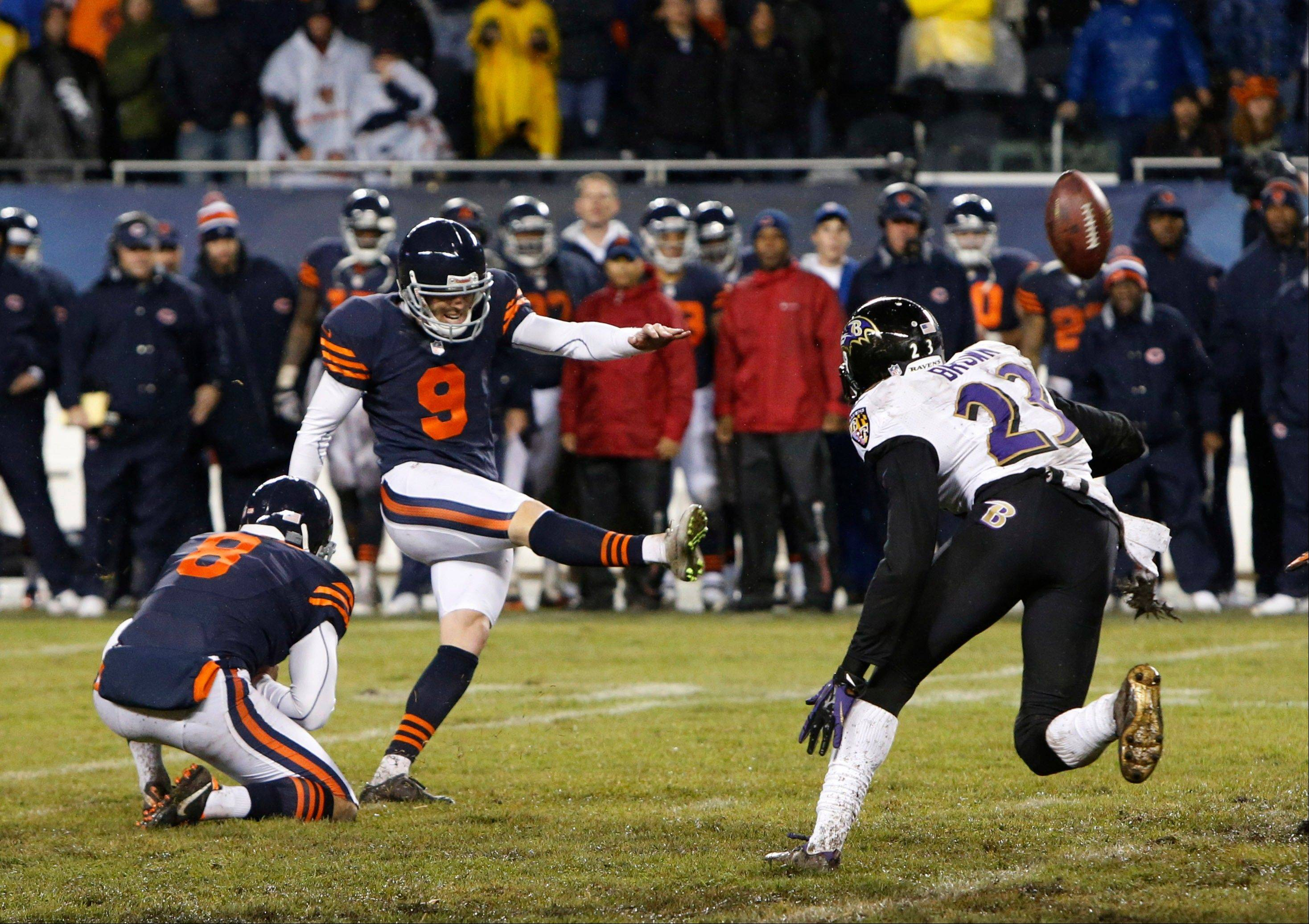 Chicago Bears kicker Robbie Gould (9) kicks the game-winning field goal in overtime to beat the Baltimore Ravens 23-20 in an NFL football game, Sunday, Nov. 17, 2013, in Chicago. Holding the ball is punter Adam Podlesh (8). At right is Ravens defensive back Chykie Brown (23).