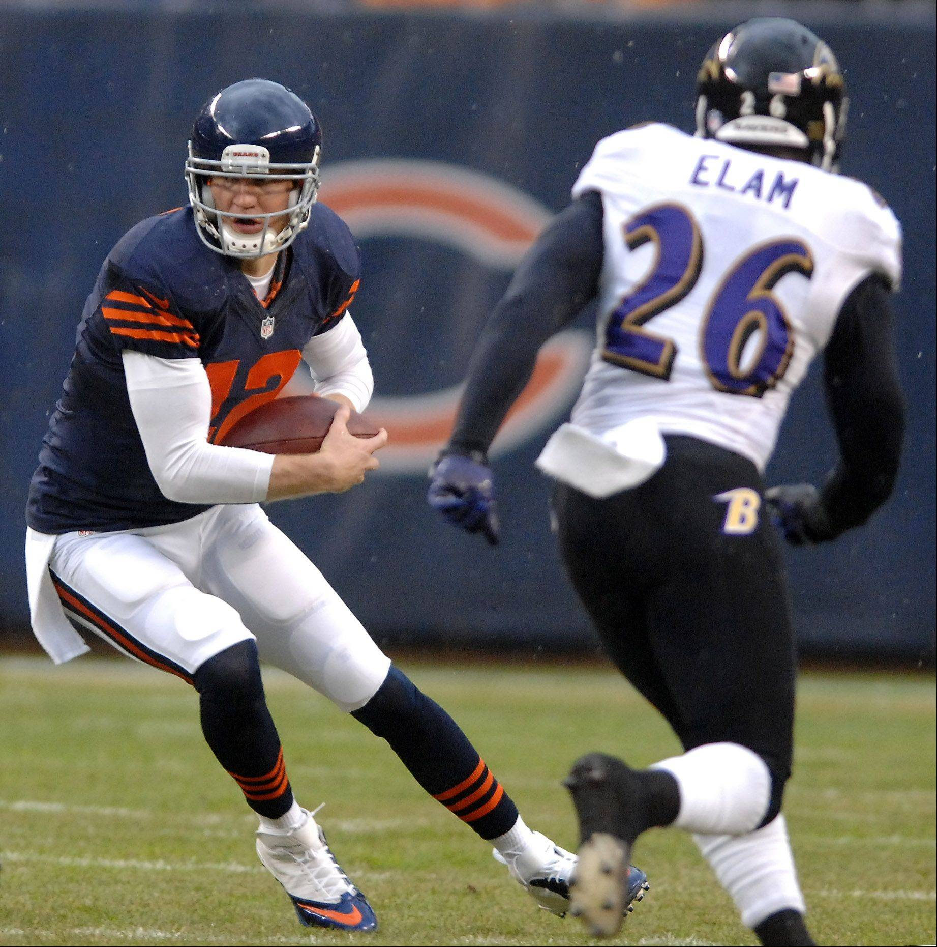 Chicago Bears quarterback Josh McCown (12) tucks and runs as he eludes Baltimore Ravens free safety Matt Elam (26) during Sunday's game in Chicago.