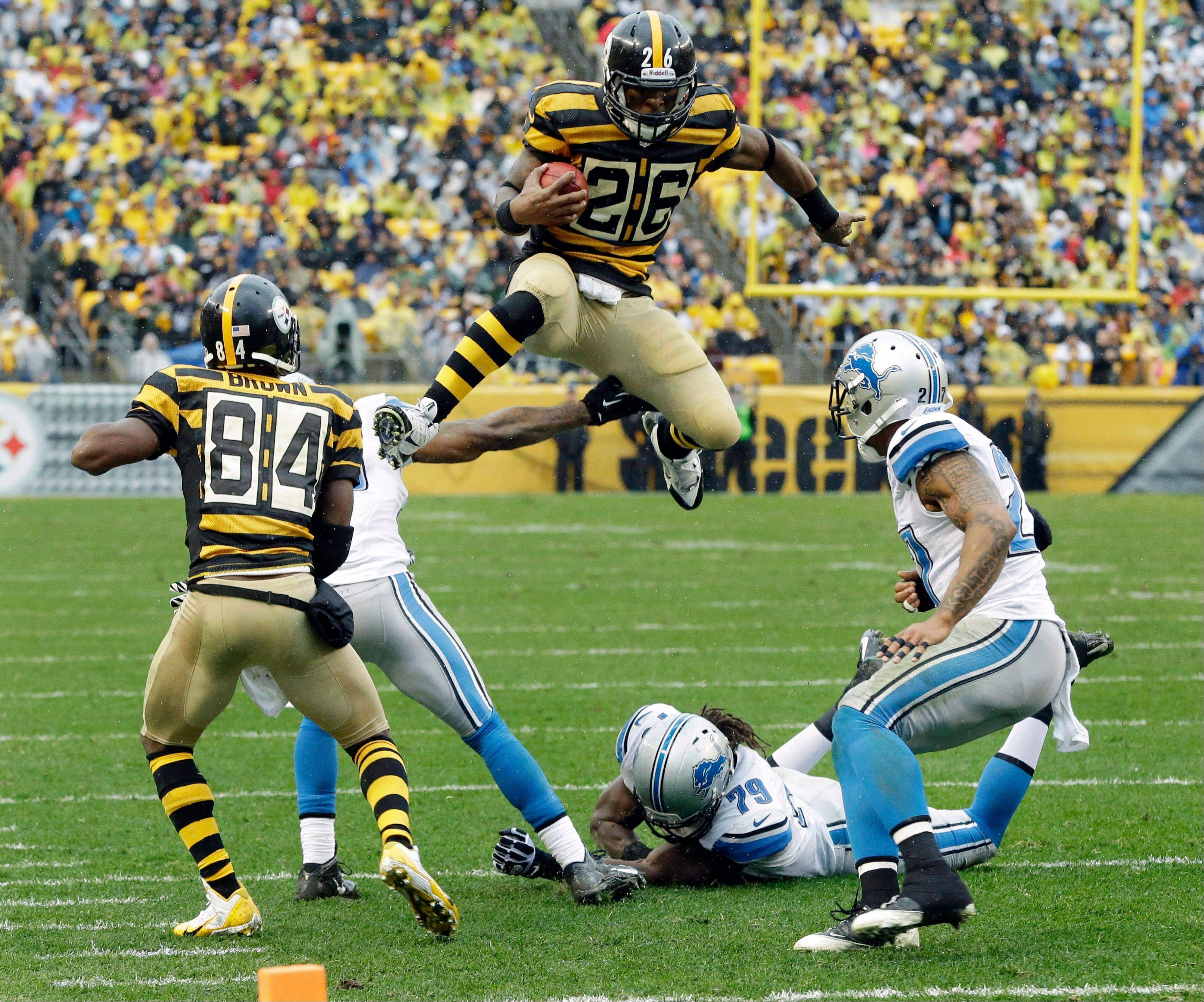 Pittsburgh Steelers running back Le'Veon Bell (26) leaps for more yardage as he tries to evade Detroit Lions strong safety Glover Quin (27) and the defense in the first half of an NFL football game in Pittsburgh, Sunday, Nov. 17, 2013.