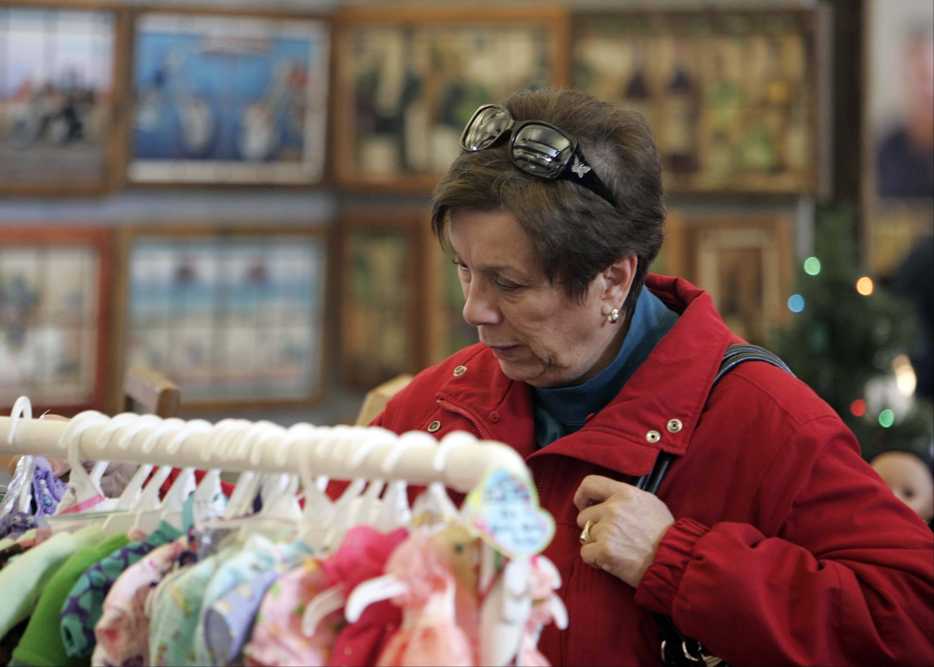 Angela Bell of Warrenville looks over some doll clothes during last year's Christmas on the Fox juried art and craft show at the Kane County Fairgrounds in St. Charles. Bell was helping a friend find some handmade doll clothes for her granddaughter.