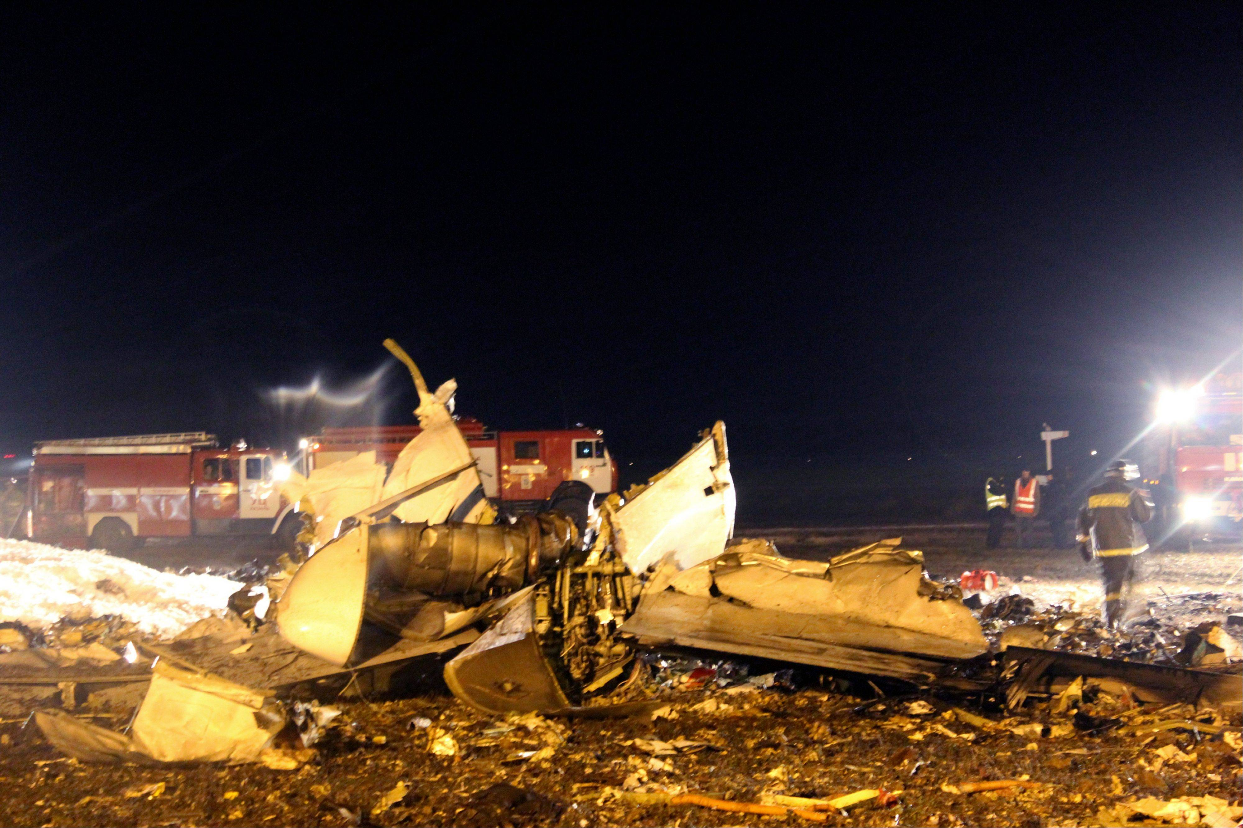 In this photo provided by Russian Emergency Situations Ministry, firefighters and rescuers work at the crash site of a Russian passenger airliner near Kazan, the capital of the Tatarstan republic, about 450 miles east of Moscow.