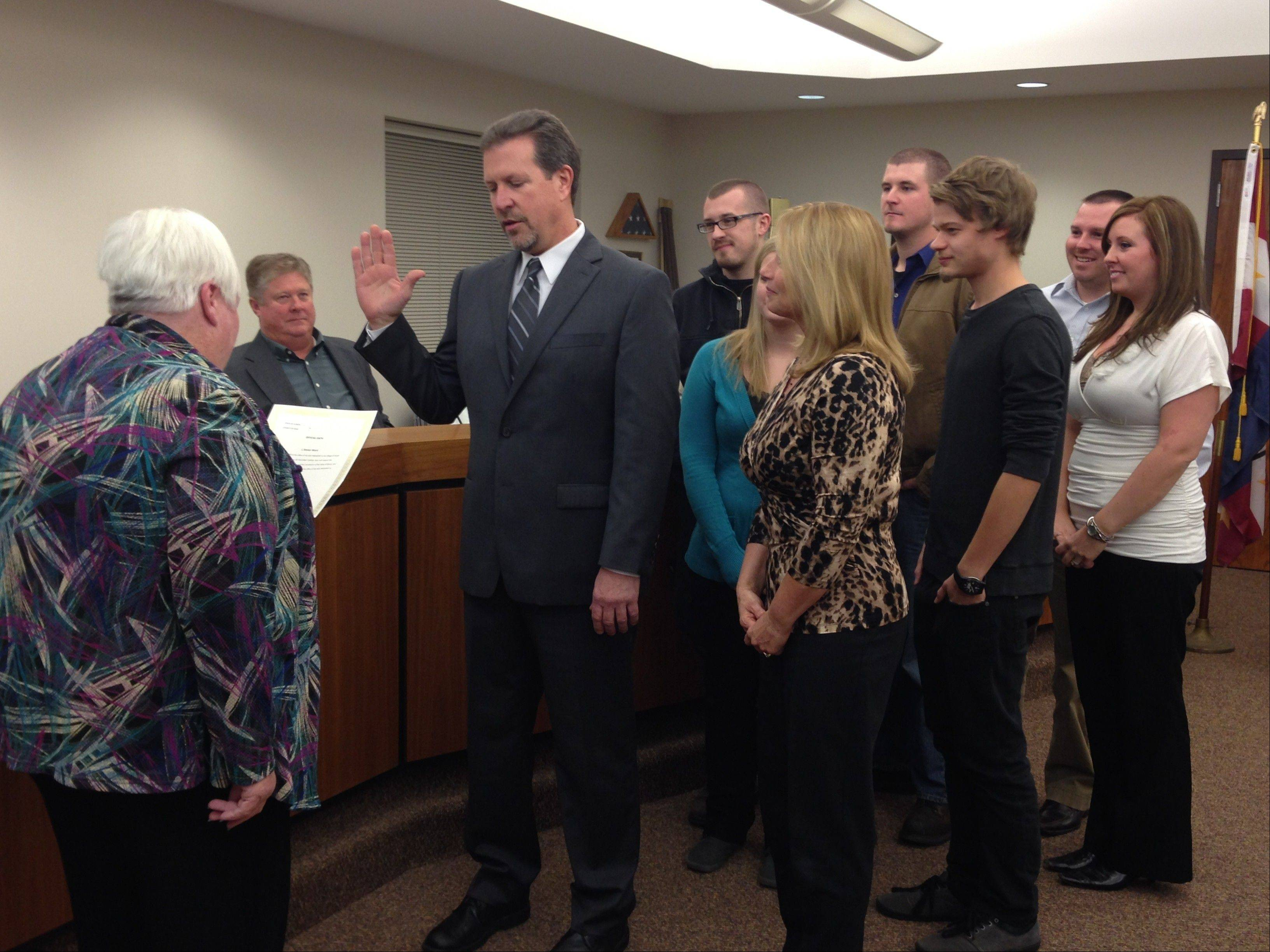New South Elgin Village President Steve Ward, surrounded by his fiancee and family, is sworn into office by Village Clerk Margo Gray on Monday night.