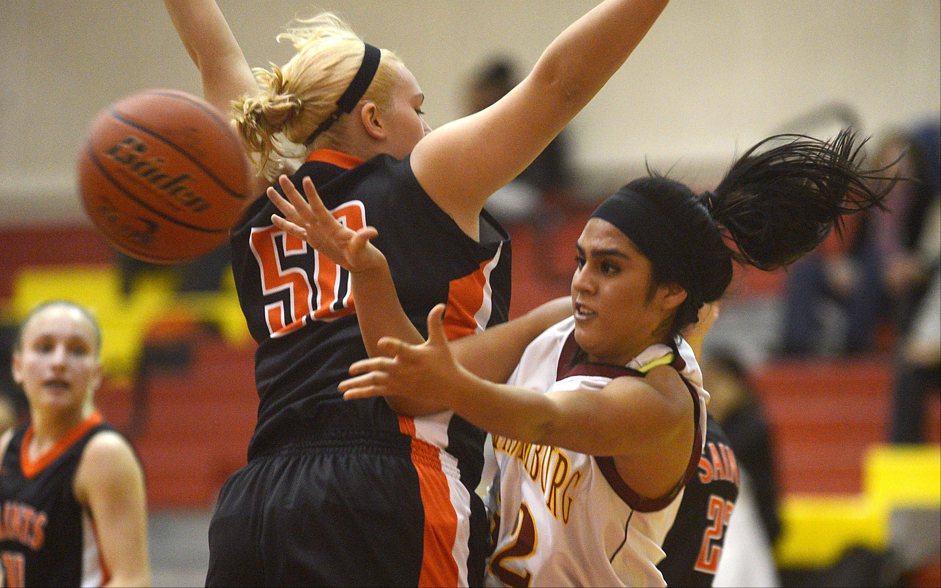 St. Charles East�s Chloe John plays defense as Schaumburg�s Lillian Chavarria, right, dishes the ball past during a varsity girls basketball game at Schaumburg High School on Monday evening.