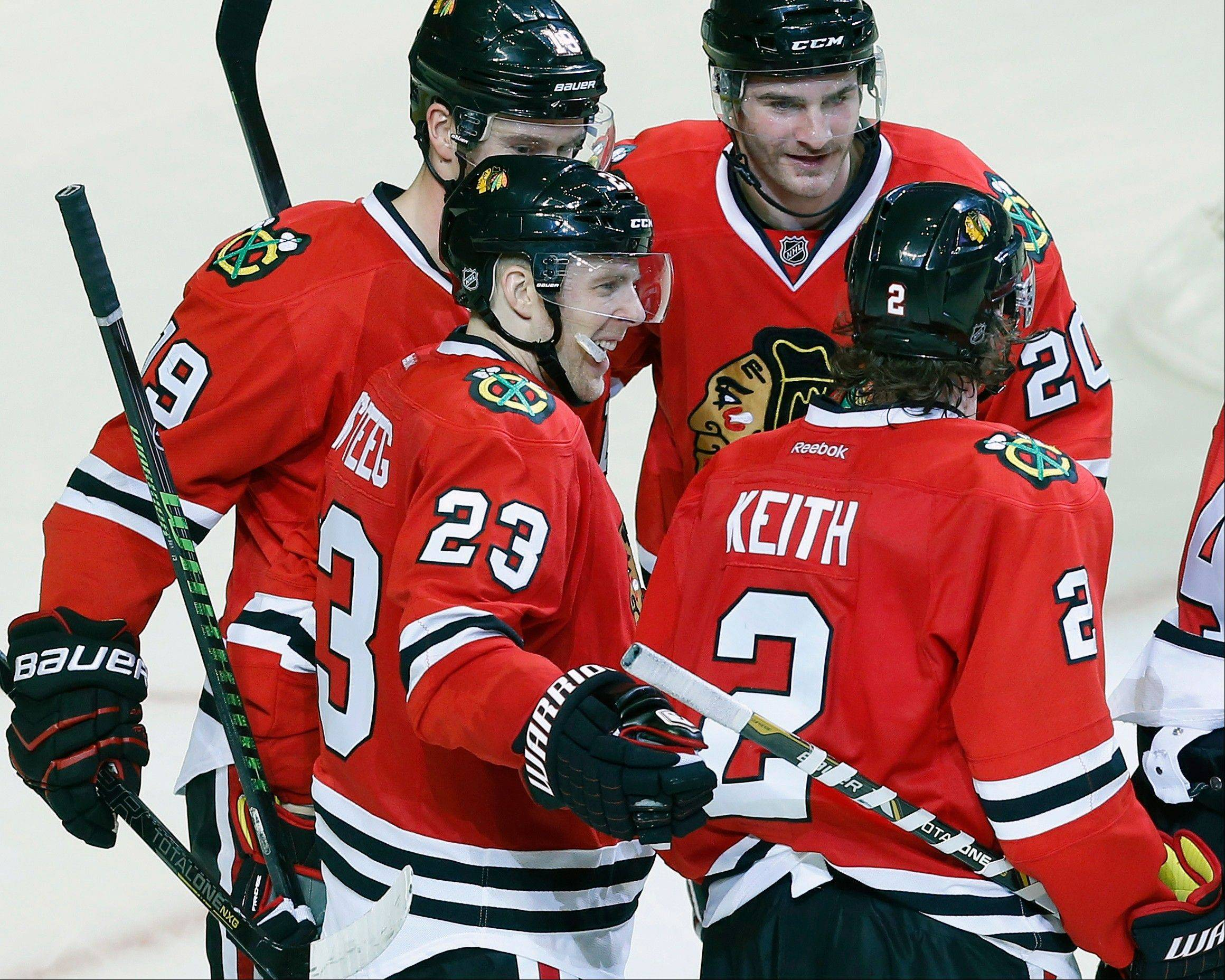 Chicago Blackhawks right wing Kris Versteeg (23) celebrates with teammates after scoring a goal against the San Jose Sharks during the third period of an NHL hockey game on Sunday, Nov. 17, 2013, in Chicago. (AP Photo/Andrew A. Nelles)