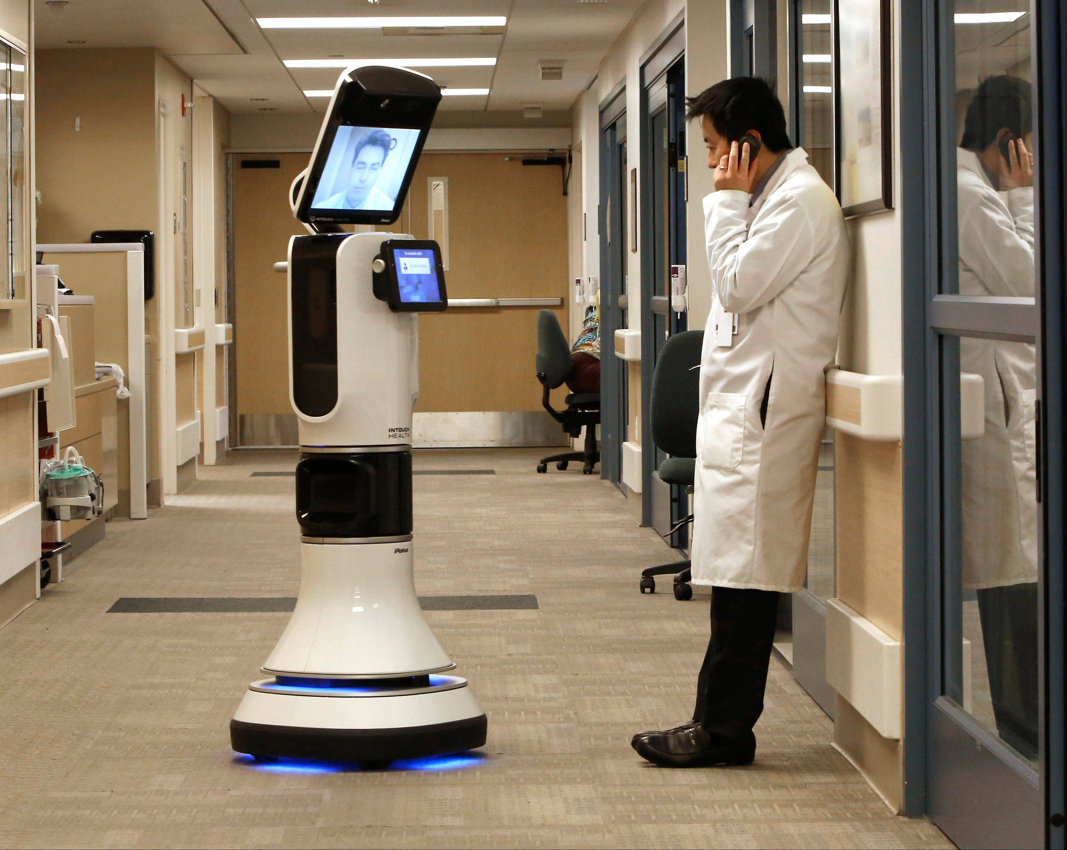 Dr. Alan Shatzel, medical director of the Mercy Telehealth Network, on the monitor RP-VITA robot as he waits to confer with Dr. Alex Nee at Mercy San Juan Hospital in Carmichael, Calif.