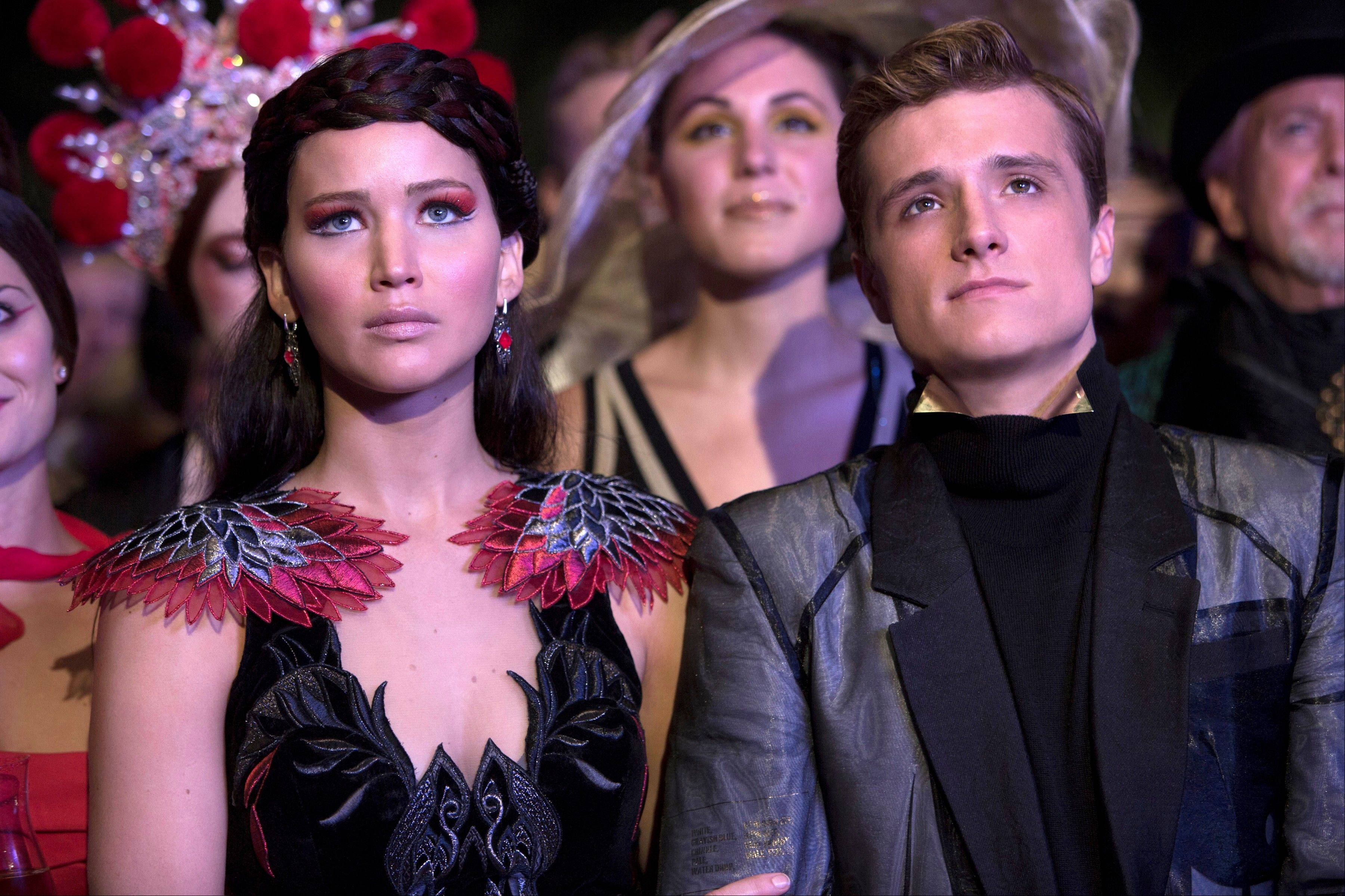 "Katniss Everdeen (Jennifer Lawrence) and her co-winner Peeta (Josh Hutcherson) prepare for another round of killing as sport in ""The Hunger Games: Catching Fire."""