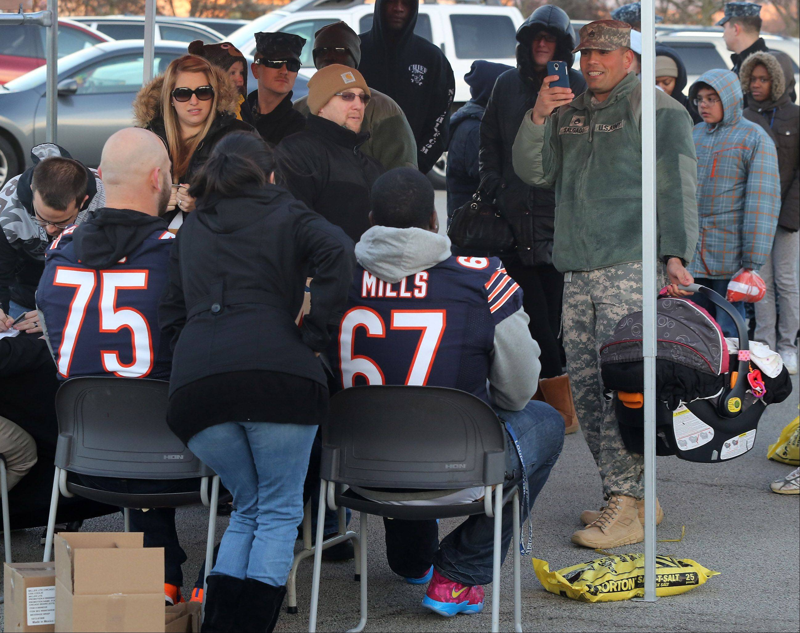 Army Sgt. Jayson Salgado holds his 3-month-old daughter, Gabriella, as he takes a picture of his wife, Cydmarie, with Bears rookies Kyle Long and Jordan Mills. Veterans and their families received Thanksgiving meals Monday at Jewel-Osco in Gurnee.