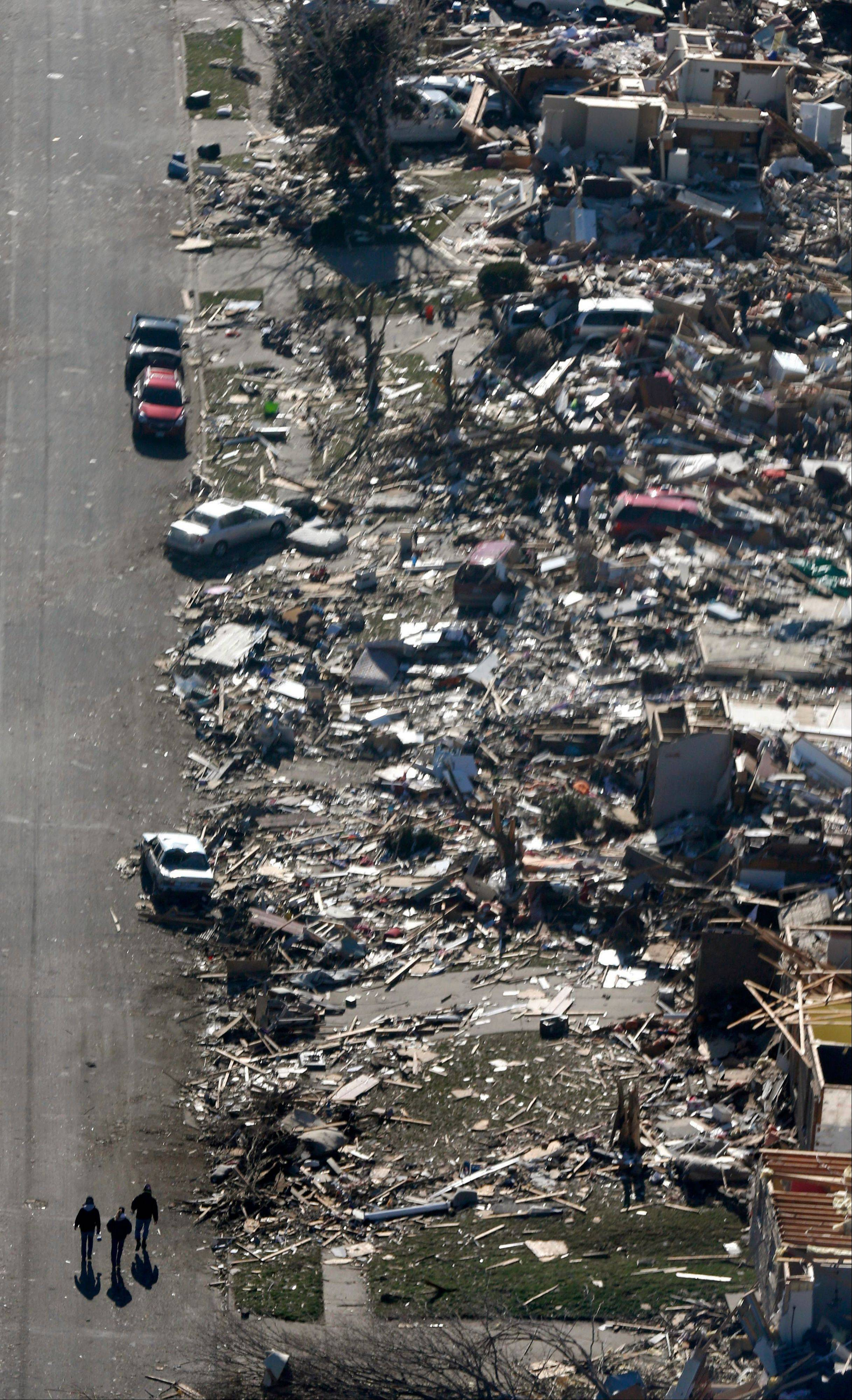 This aerial view on Monday, Nov. 18, 2013, shows three people walking down a street where homes were destroyed by a tornado that hit the western Illinois town of Washington on Sunday. It was one of the worst-hit areas after intense storms and tornadoes swept through Illinois. The National Weather Service says the tornado that hit Washington had a preliminary rating of EF-4, meaning wind speeds of 170 mph to 190 mph.