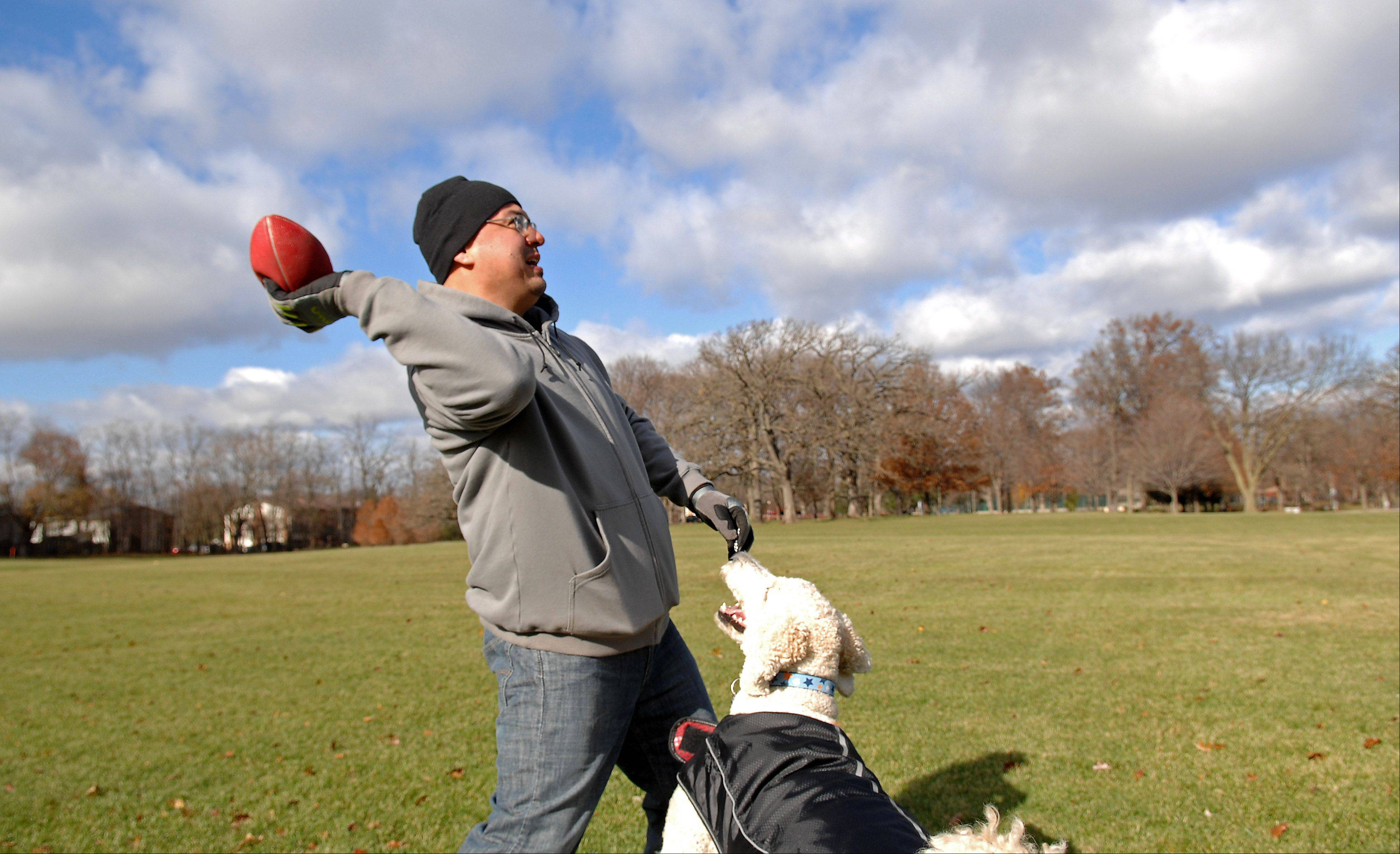 Miguel Martinez of Elgin plays catch with his family's service dog, Marley, Monday at Wing Park.