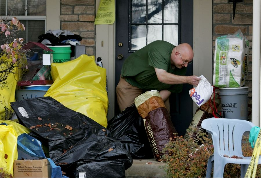David Skeberdis sifts through items on his Aurora porch in October 2012 after authorities found more than 450 living and dead birds inside his home.