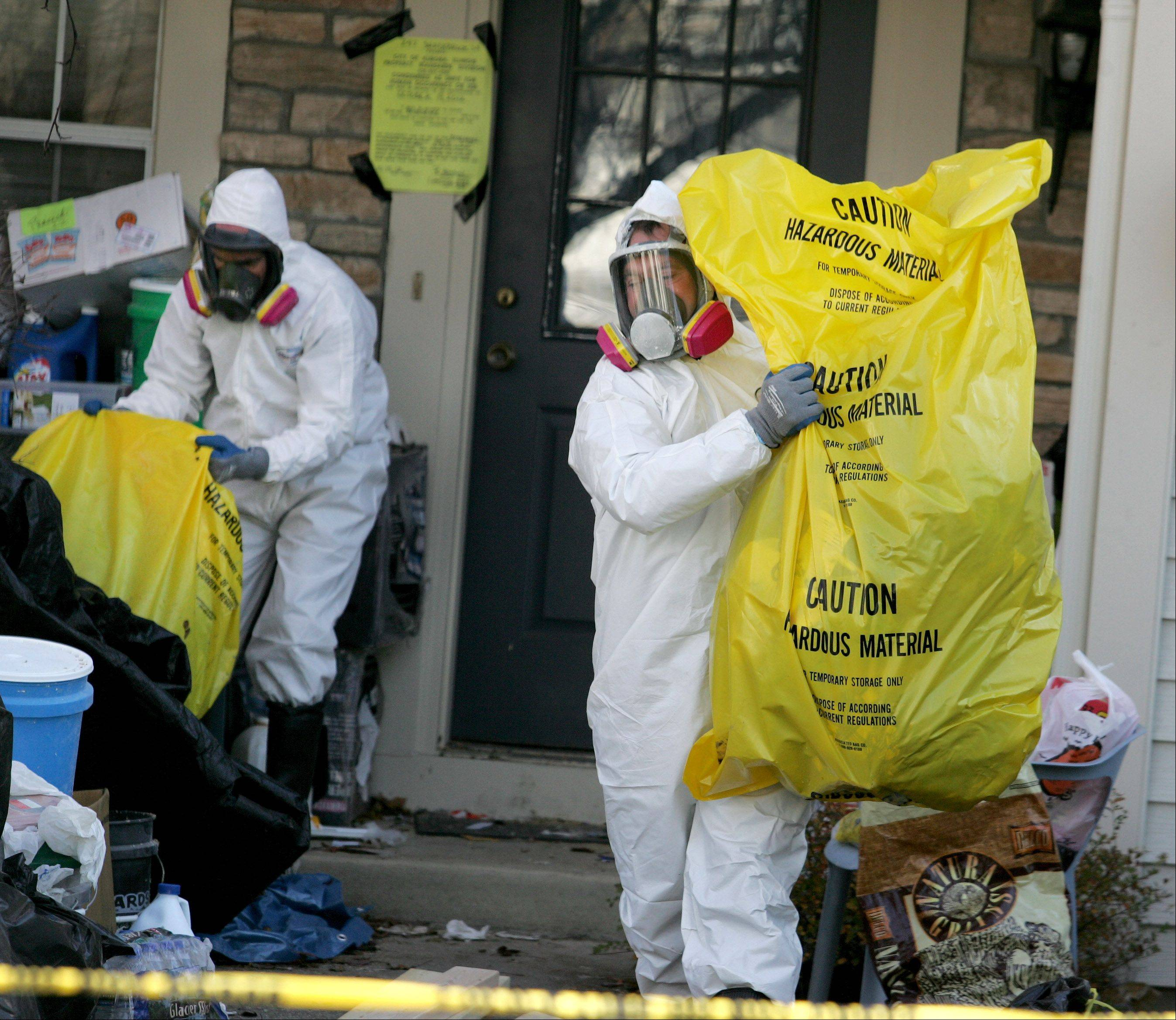 Workers from Restoration Techs remove garbage from the Aurora home of David Skeberdis in October 2012.