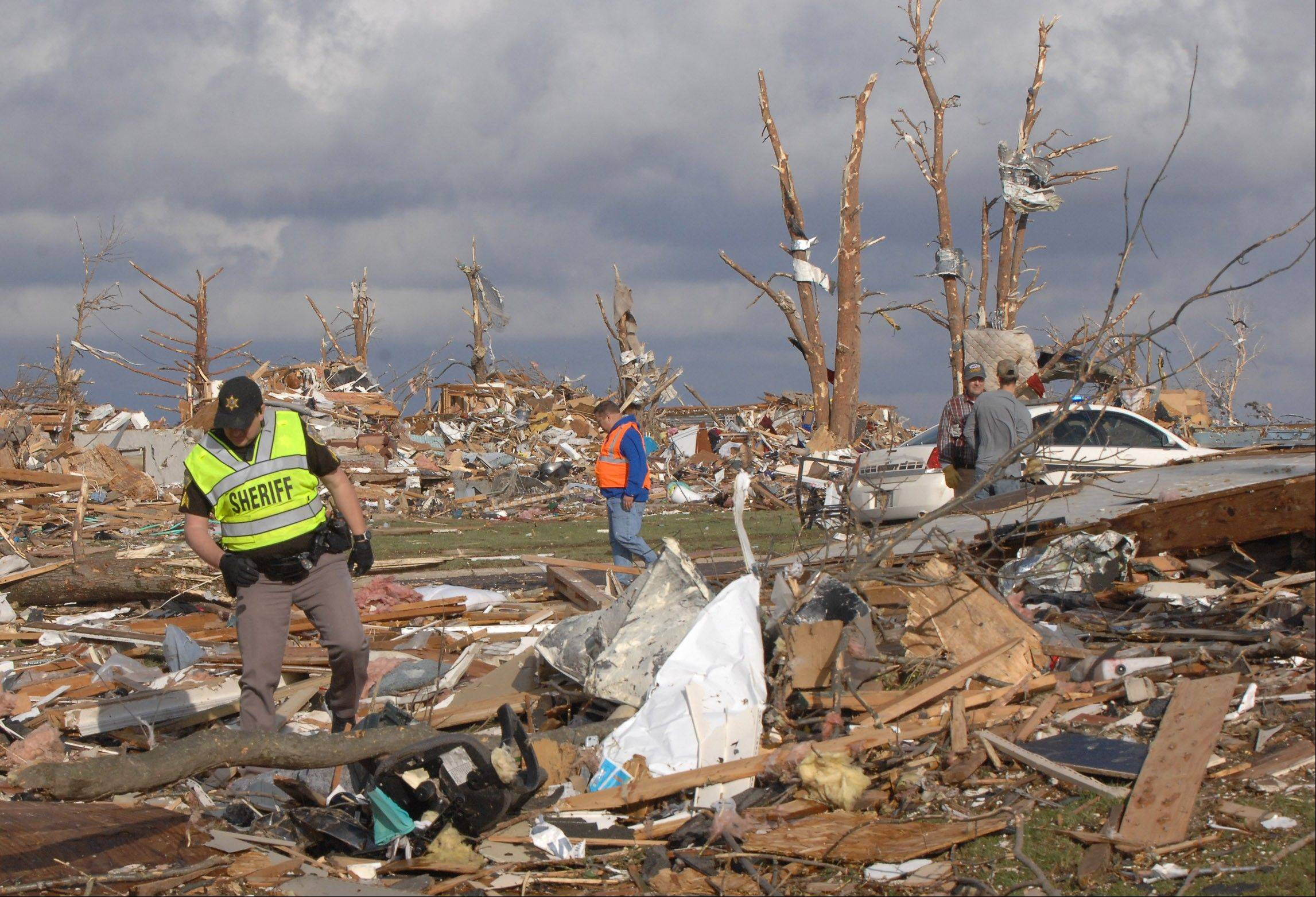 A deputy sergeant with the Tazewell County sheriff's department walks through debris Sunday in the Devonshire subdivision in Washington after a tornado that severely damaged many homes in the town east of Peoria.