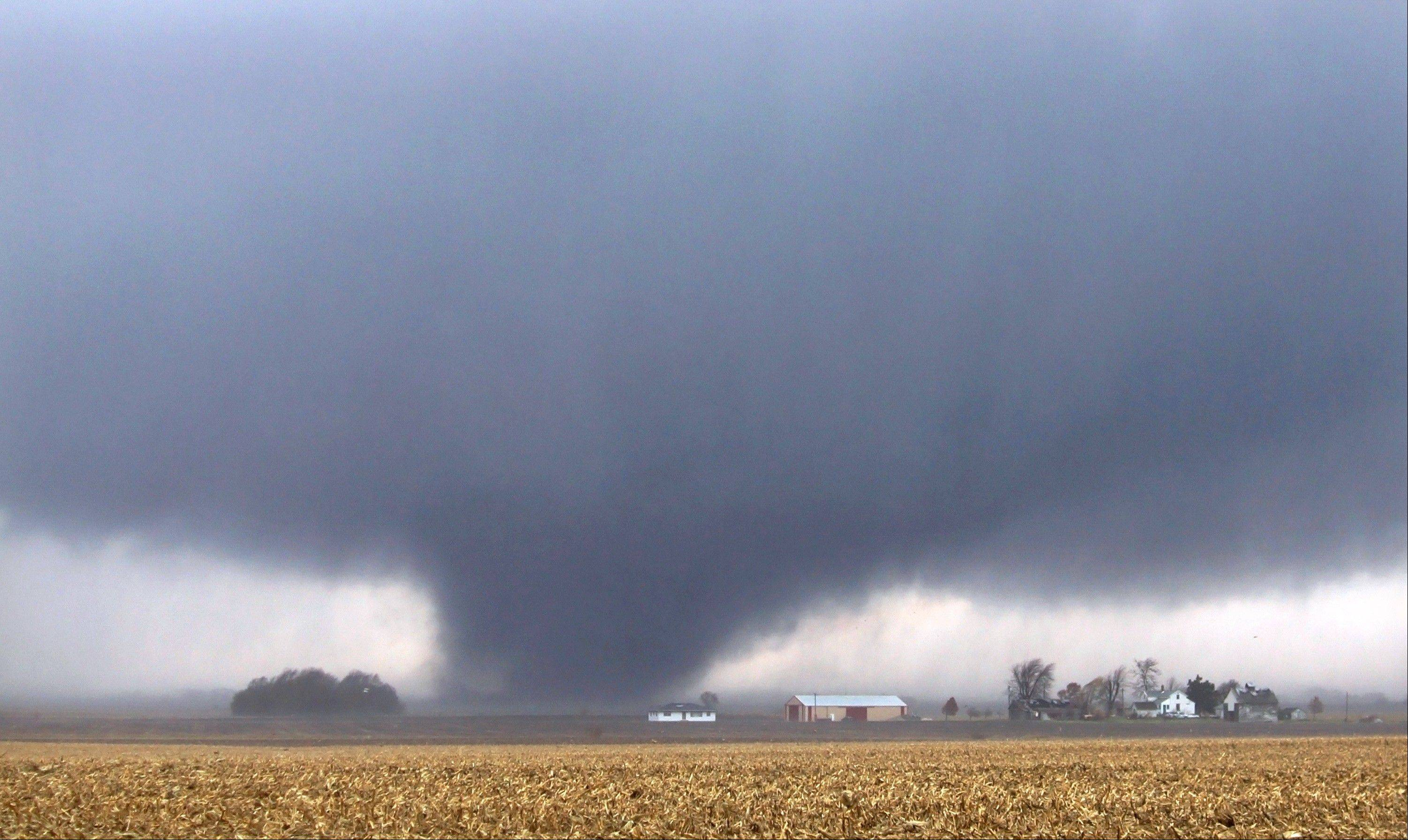 A tornado moves northeast Sunday, Nov. 17, 2013, two miles west of Flatville, Ill. The tornado damaged many farm buildings and homes on its way to Gifford, Ill., where scores of houses were devastated.