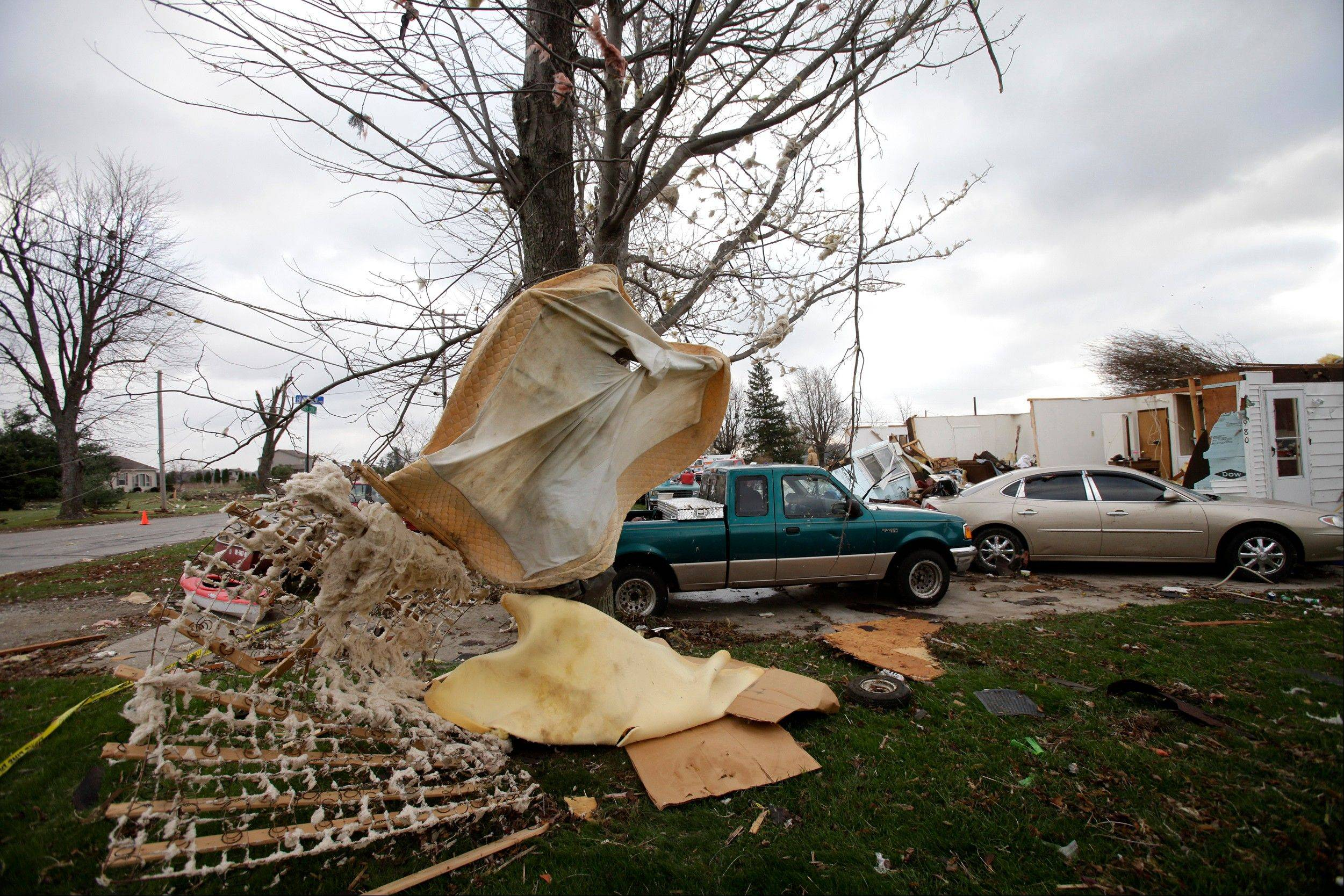 A bed mattress is seen wrapped around a tree, Monday, Nov. 18, 2013, after strong winds destroyed a home in Jerry City, Ohio. Dozens of tornadoes and intense thunderstorms swept across the U.S. Midwest on Sunday, unleashing powerful winds that flattened entire neighborhoods, flipped over cars and uprooted trees.
