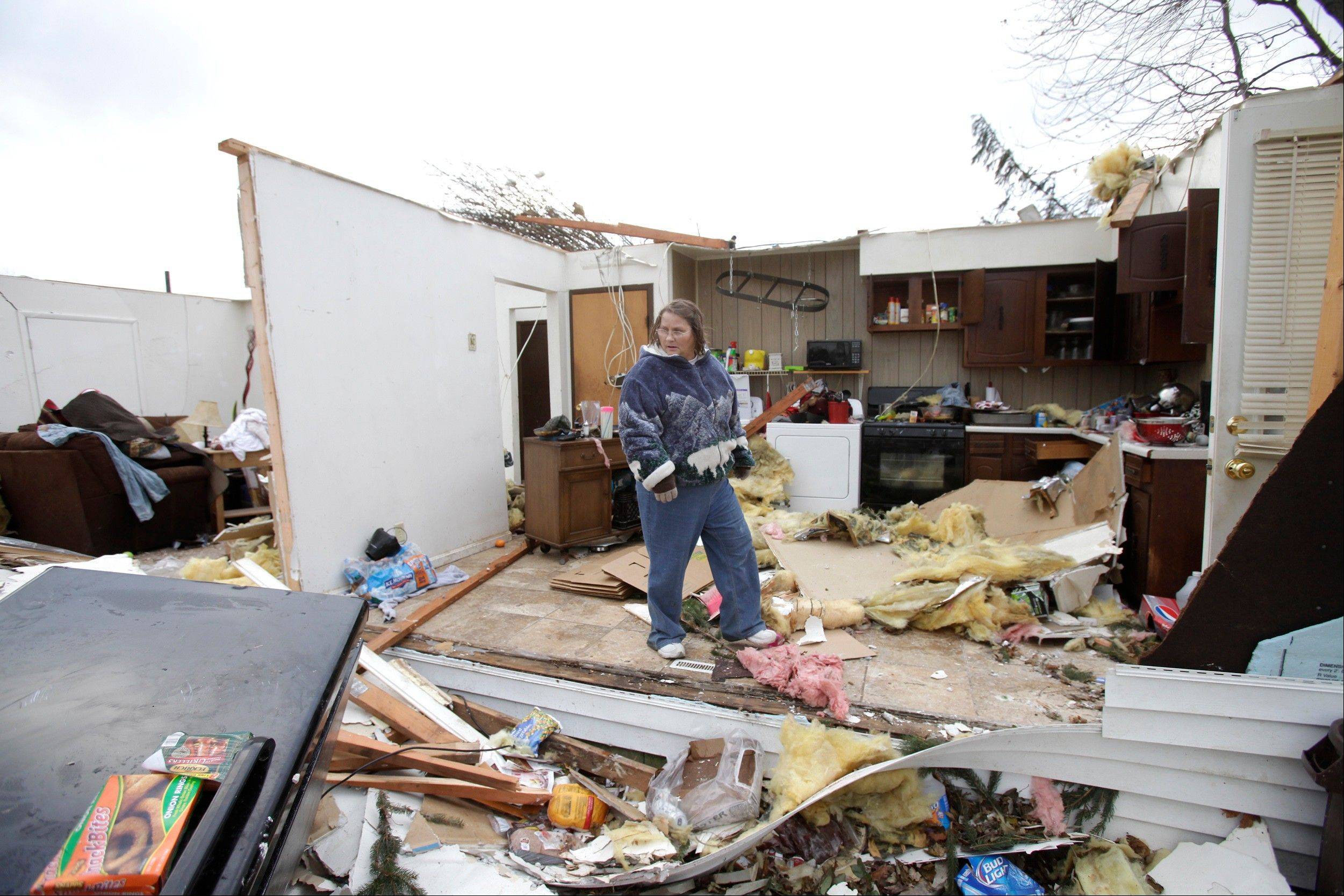 Georgia Sterling walks through what is left of her son's kitchen, Monday, Nov. 18, 2013, after strong winds destroyed this home in Jerry City, Ohio. Sterling's son, Joshua Hopple, and his wife, Carol, were both in the house when high winds ripped through the home. Dozens of tornadoes and intense thunderstorms swept across the U.S. Midwest on Sunday, unleashing powerful winds that flattened entire neighborhoods, flipped over cars and uprooted trees.