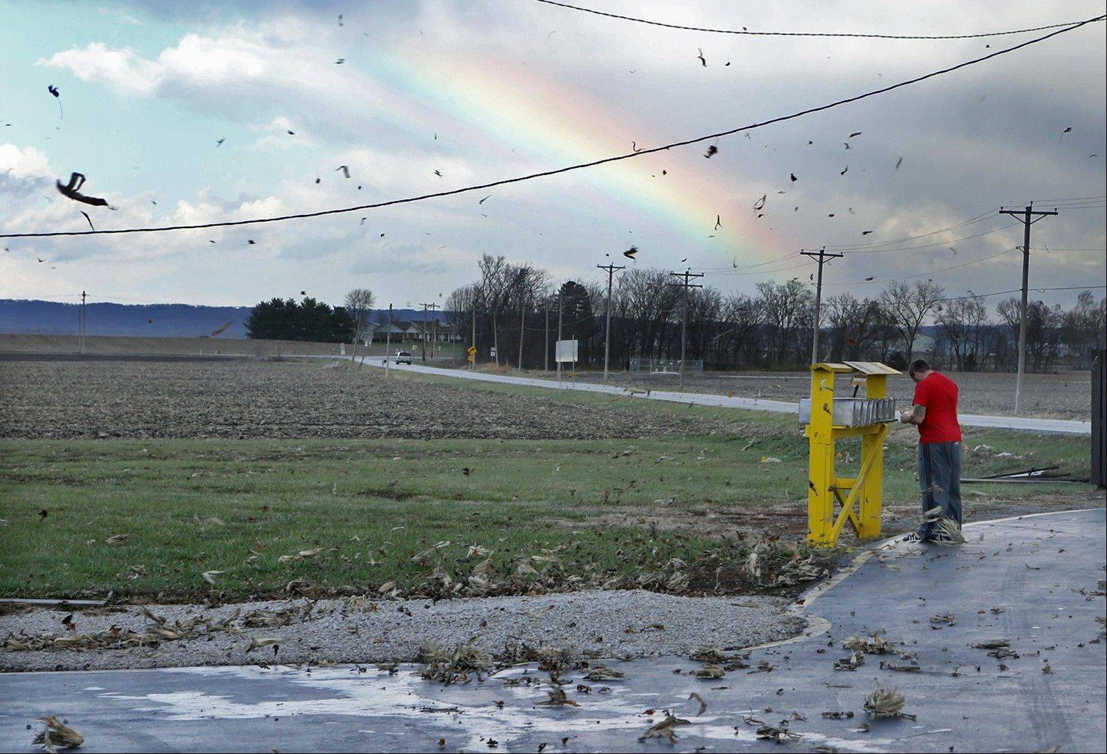 Eric Crawford, 28, waited for the storm to pass and a rainbow to appear before checking on his mail in rural Orchard Farm on Sunday, Nov. 17, 2013, in St. Charles County. Corn husks were flying through the air in the high winds.